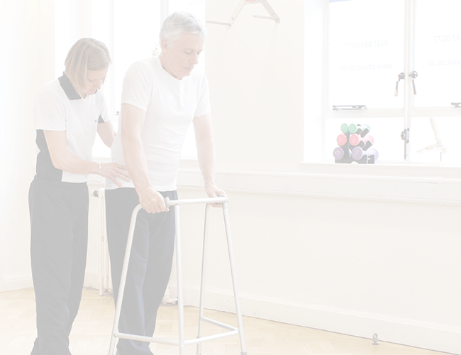 Elderly male patient recieves walking aid via trained physiotherapist and walking frame.