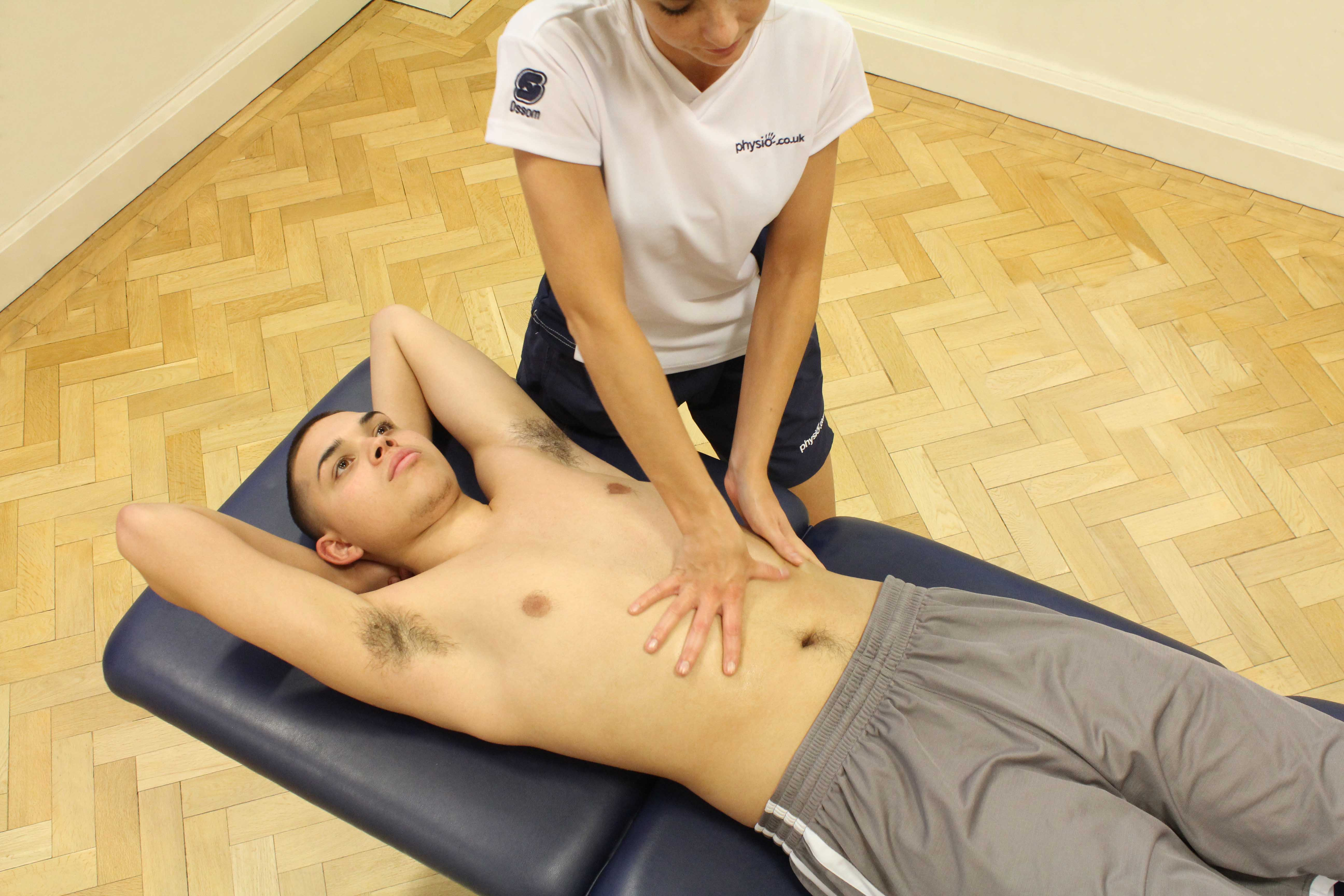 Soft tissue massage of the abdominals by therapist