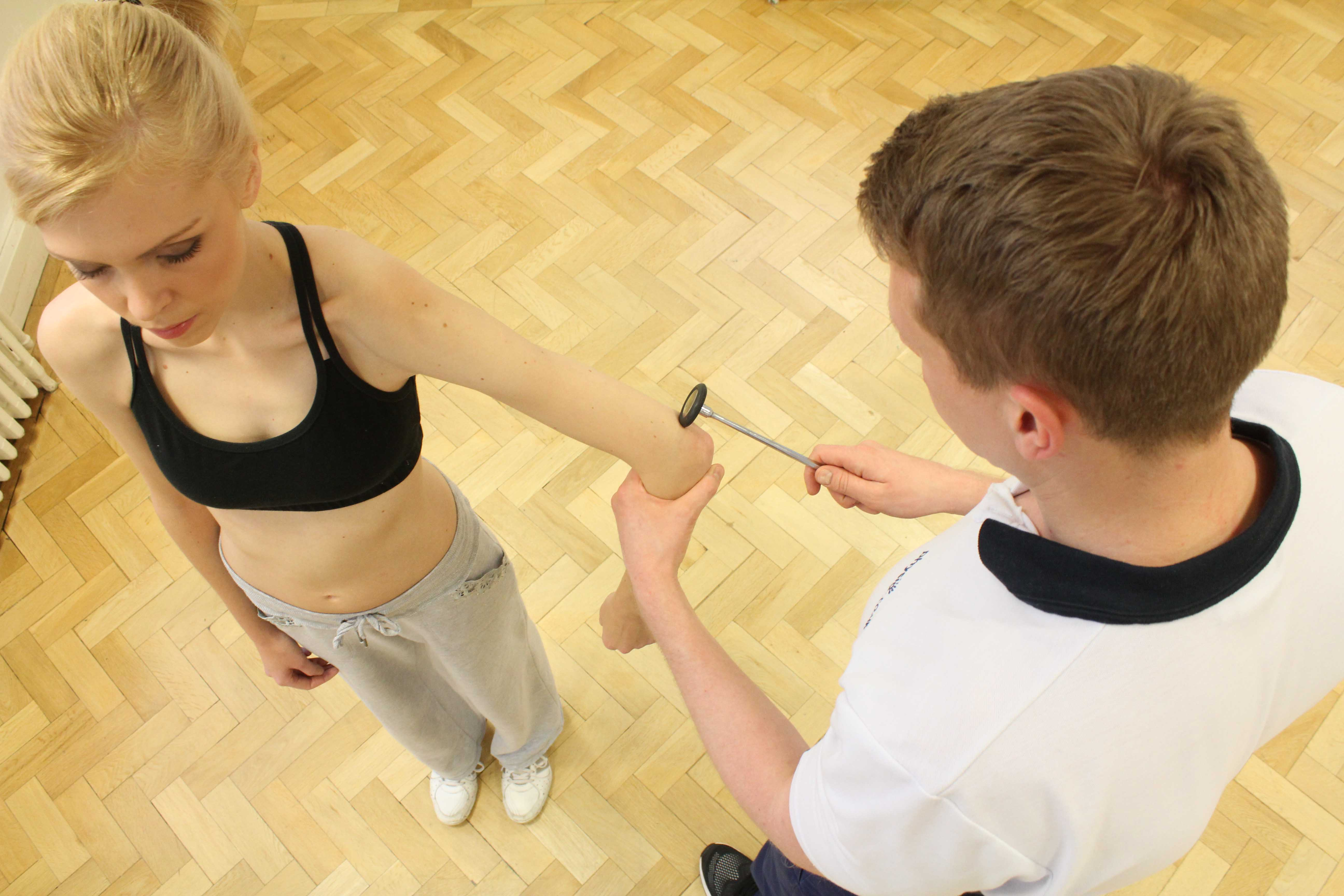 Specialist musculoskeletal Physiotherapist testing tendon reflexes at the elbow