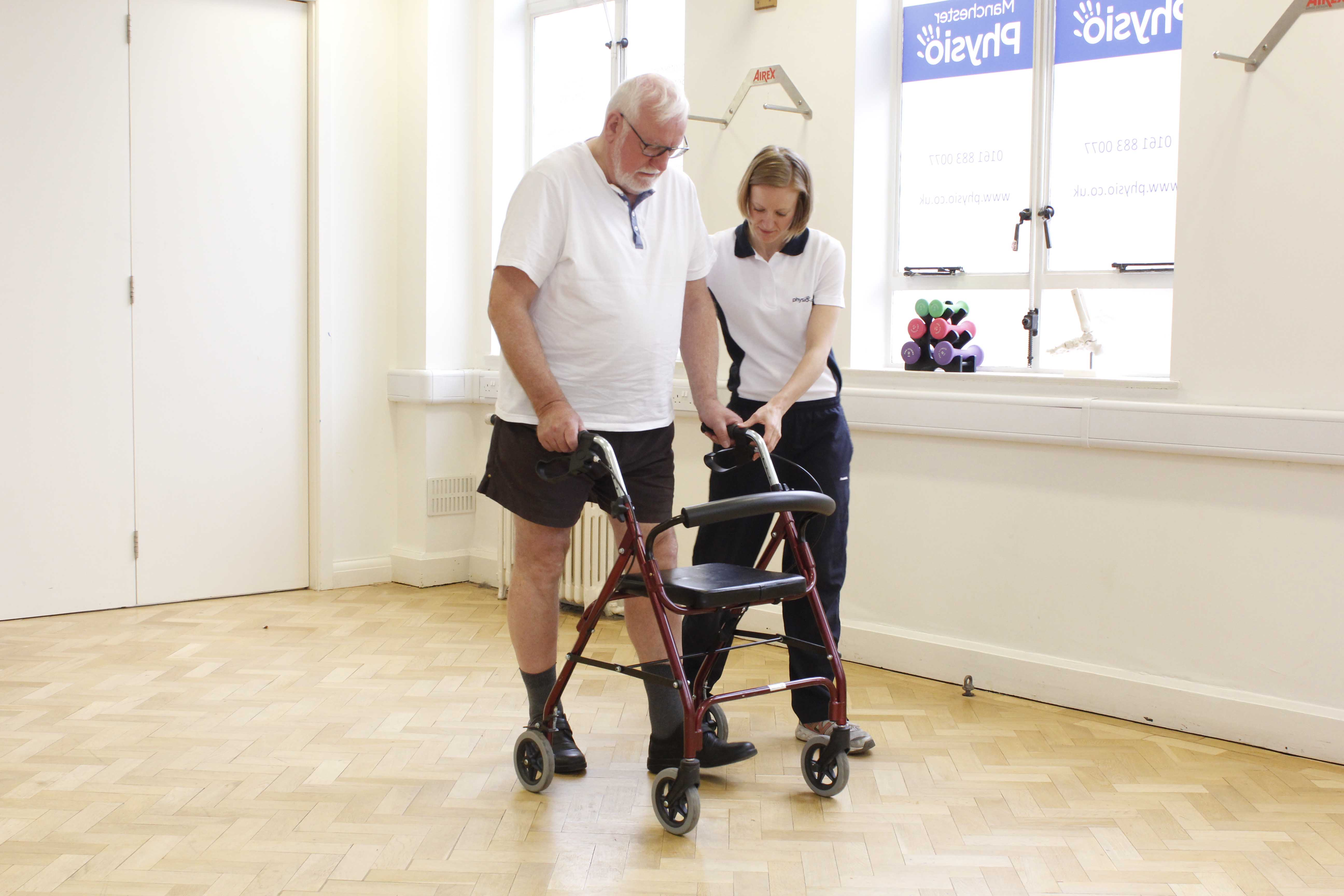 Specialist physiotherapist closely supervising mobility exercises using a rollator frame
