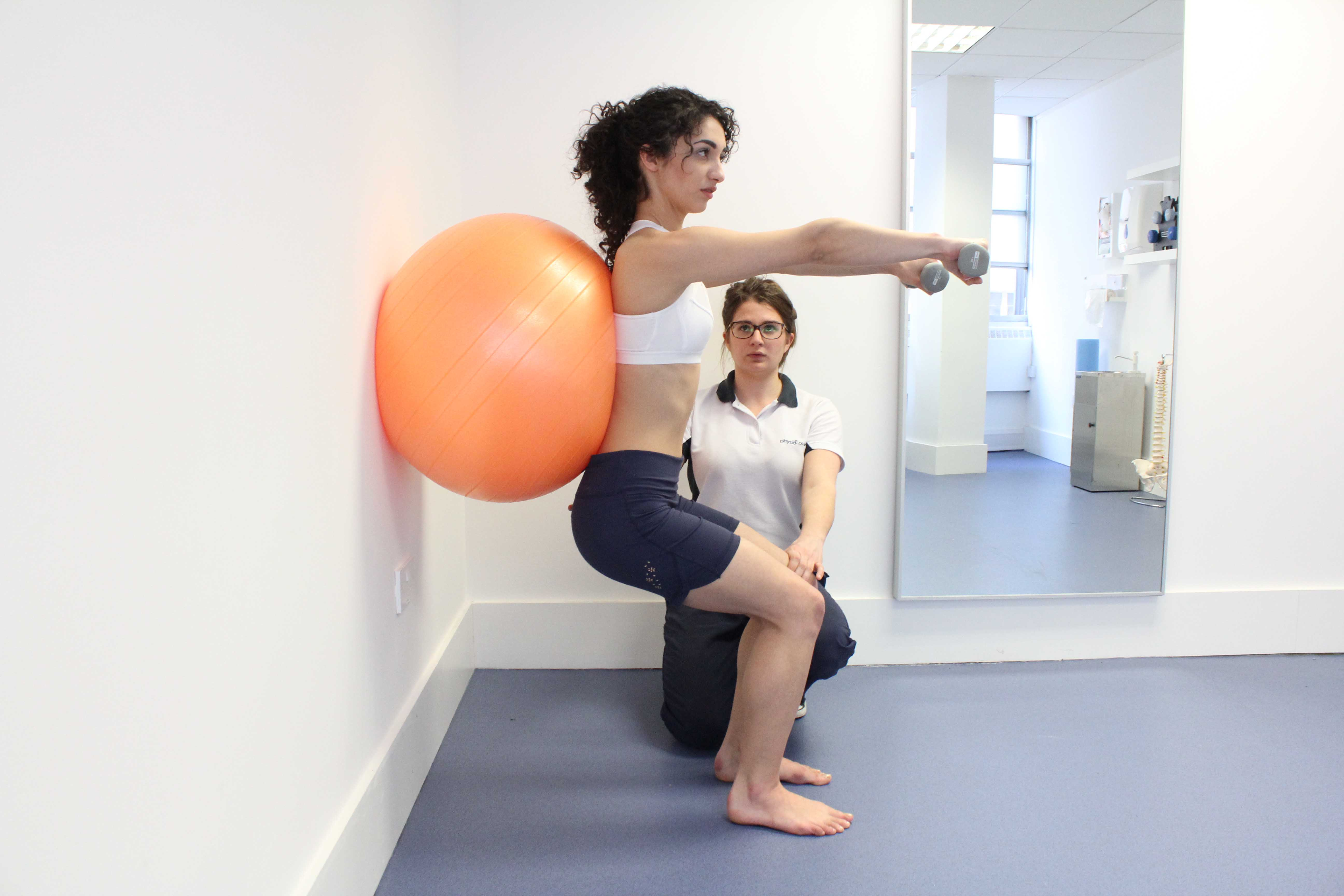 Leg strengthening exercises using squats and a gym ball with hand weights, under supervision of specialist MSK physiotherapist
