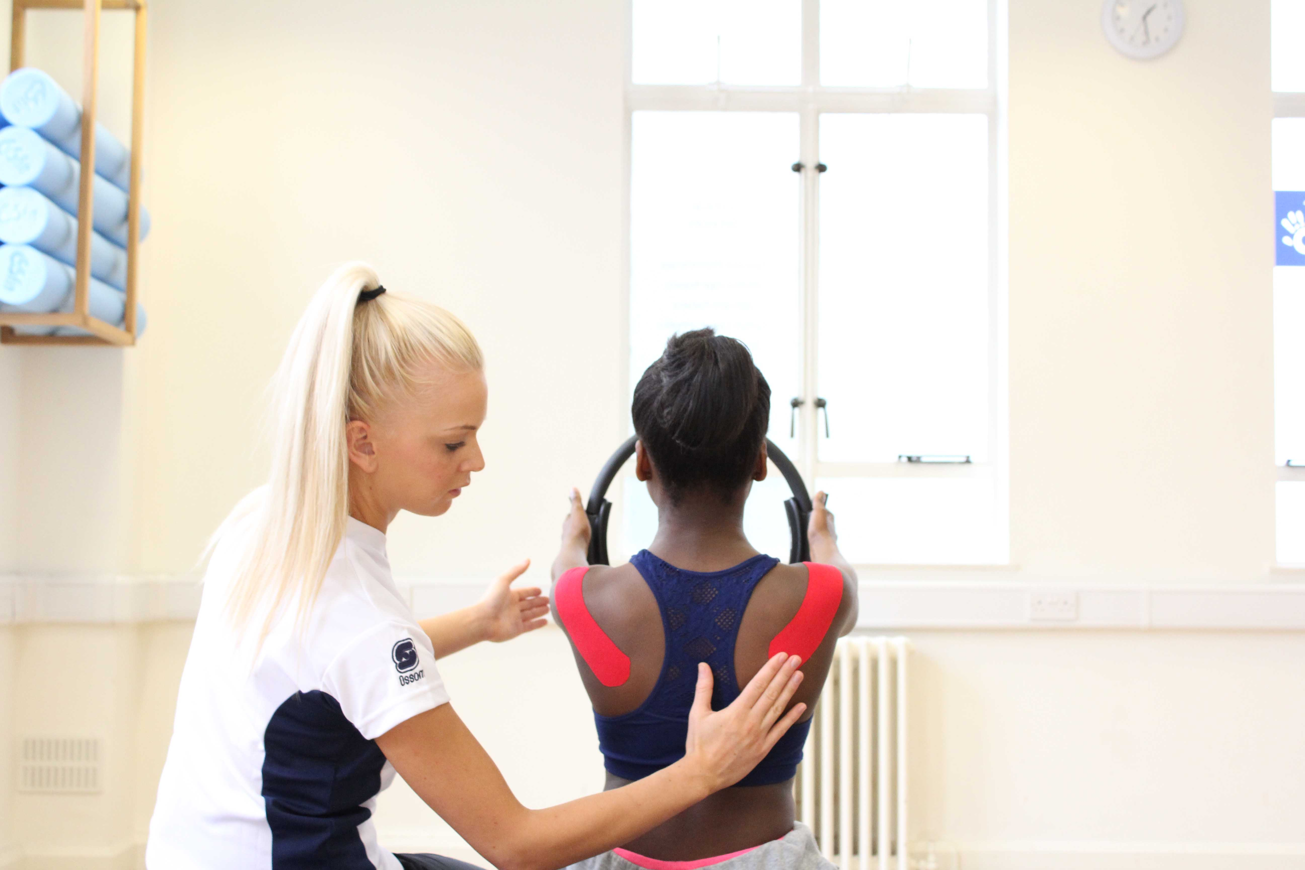 Physiotherapist using taping to help stabilise the muscles in the upper back during exercise