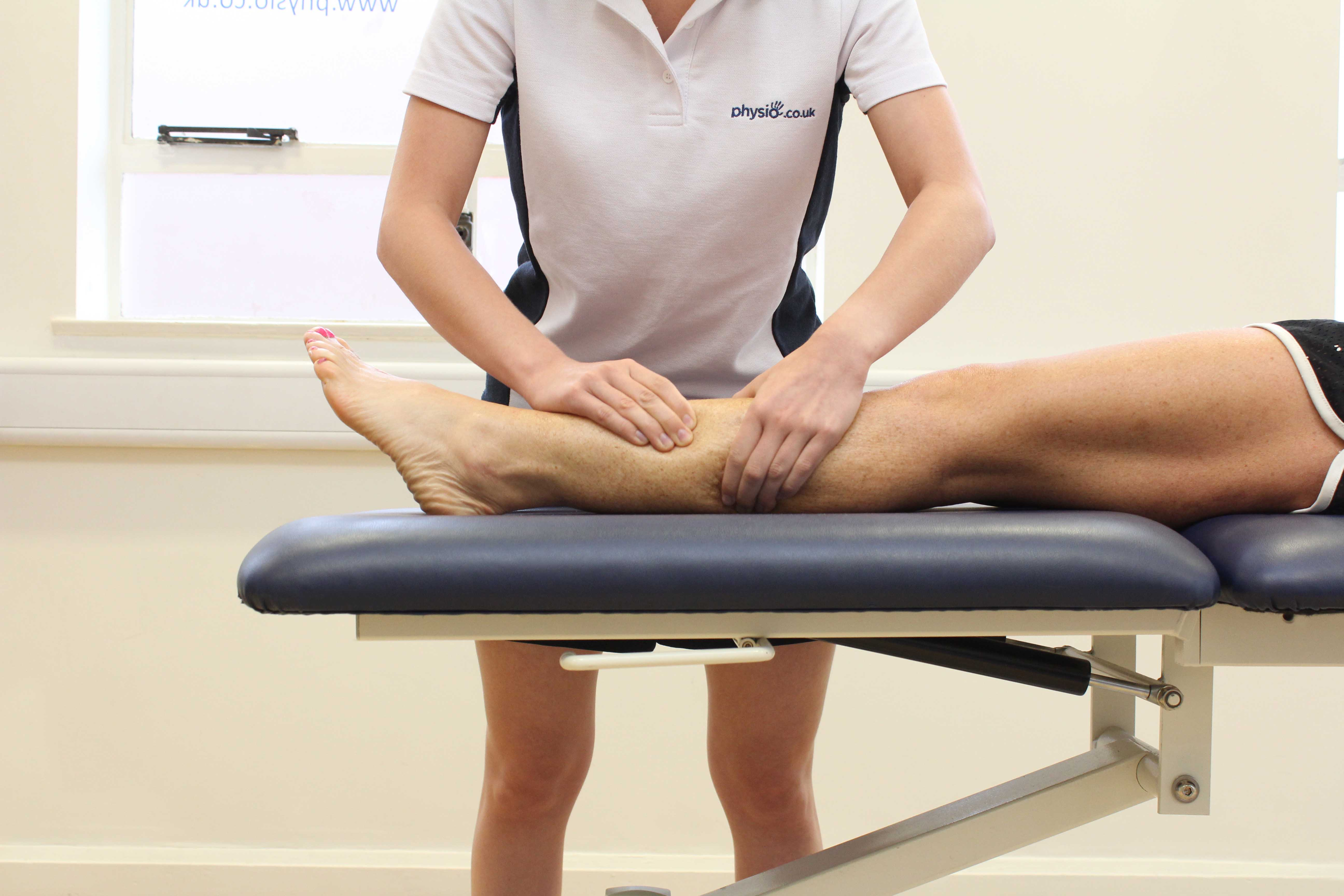 Rolling soft tissue massage of the lower leg by a specialist massage therapist