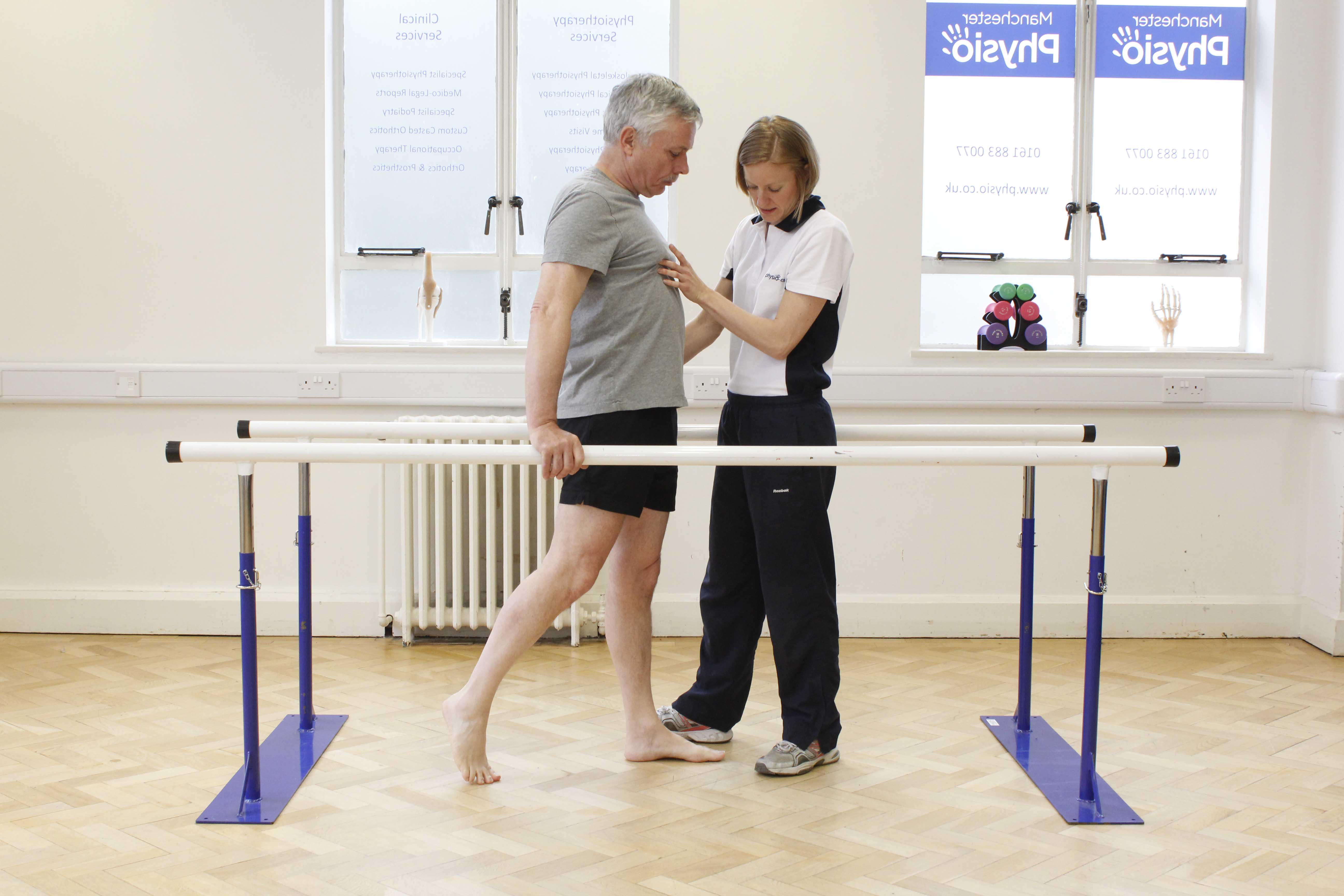 Specialist physiotherapist supervising mobilisation exercises between the parallel bars