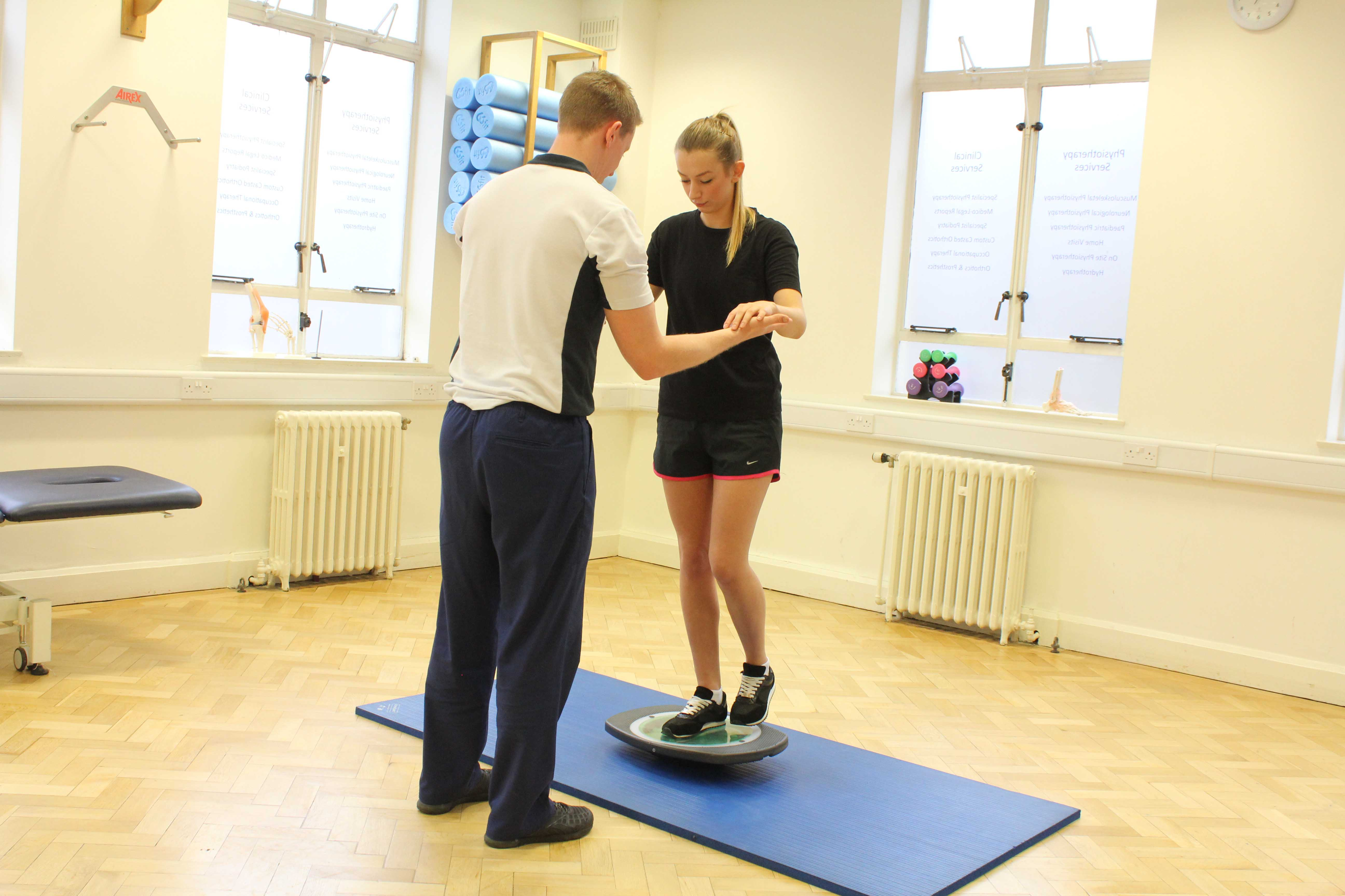 Physiotherapist using a wobble board to retrain a clients core stability