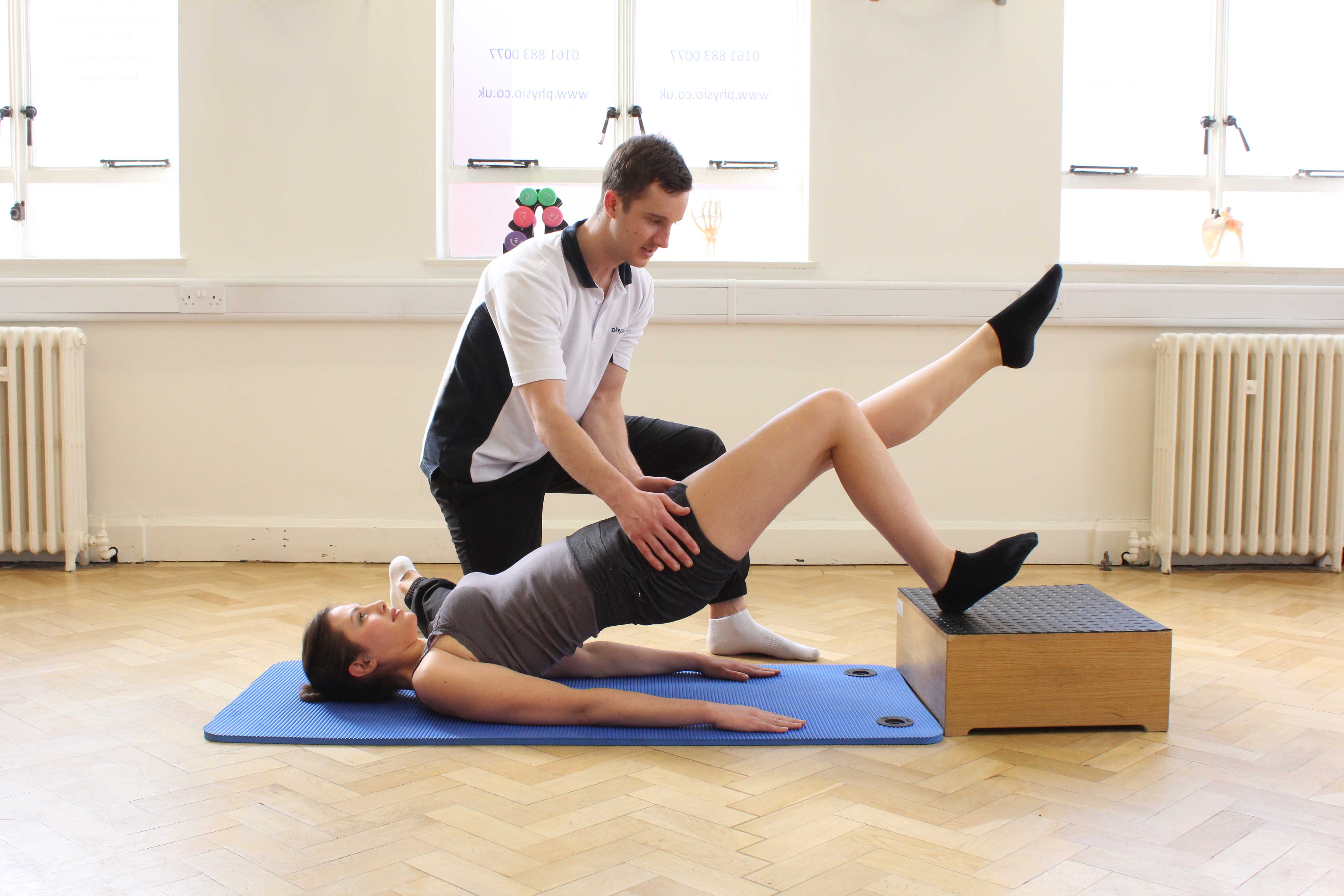 Specilaist physiotherapist supervising core stability exercises