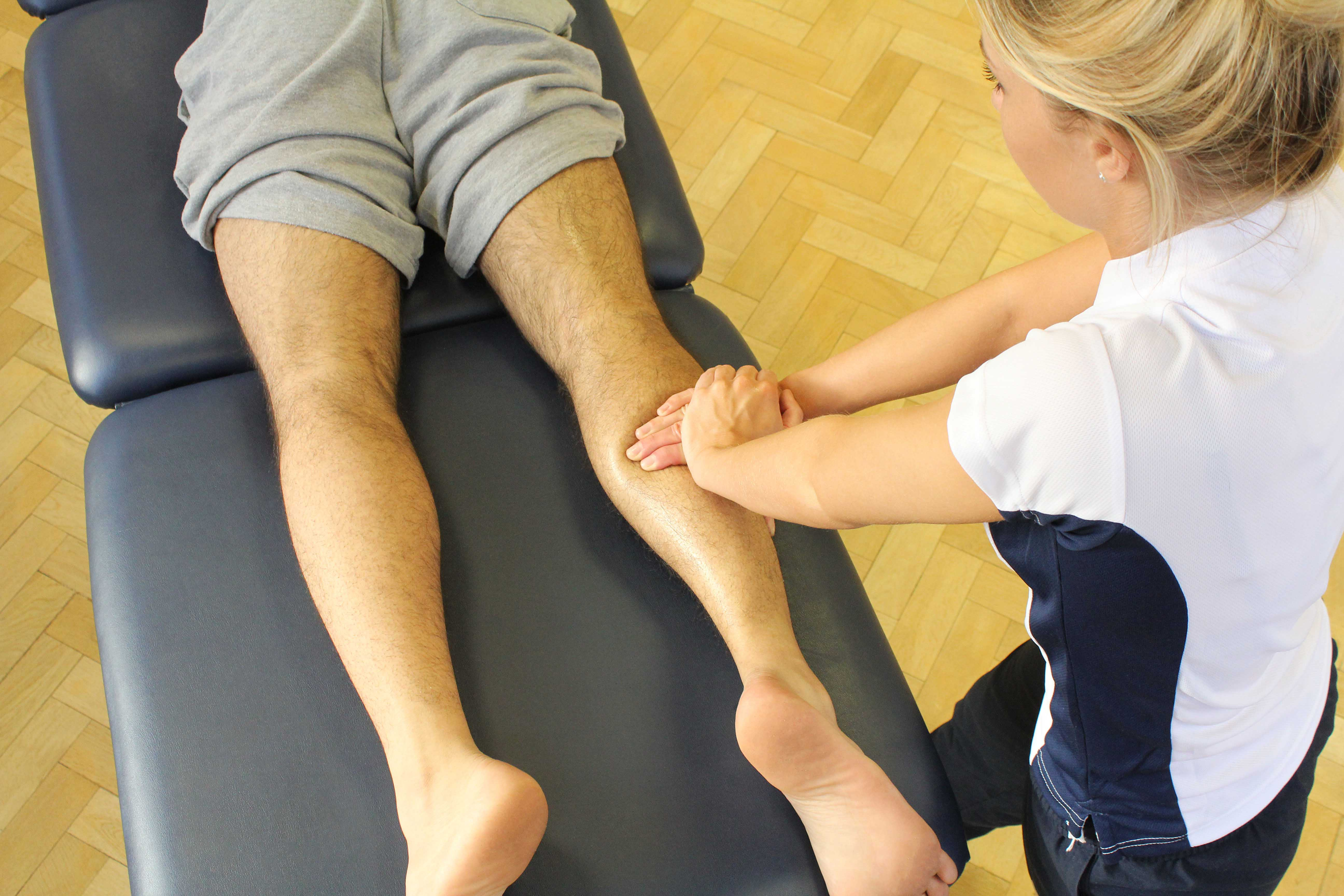 Deep tissue massage of the gastrocnemius muscle to relieve cramps and aching