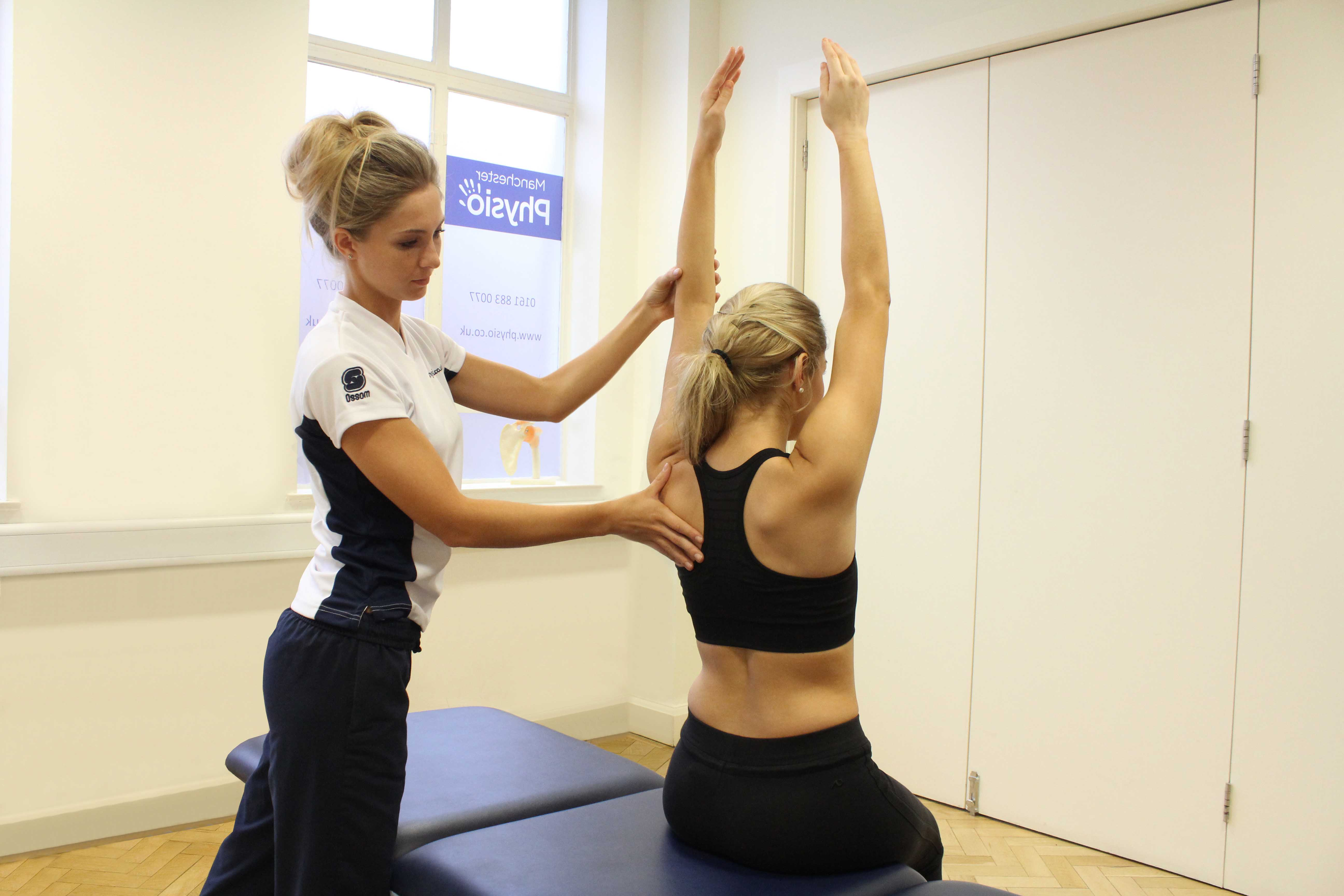 Specialist MSK therapist assessing scapula position and movement for any deformities