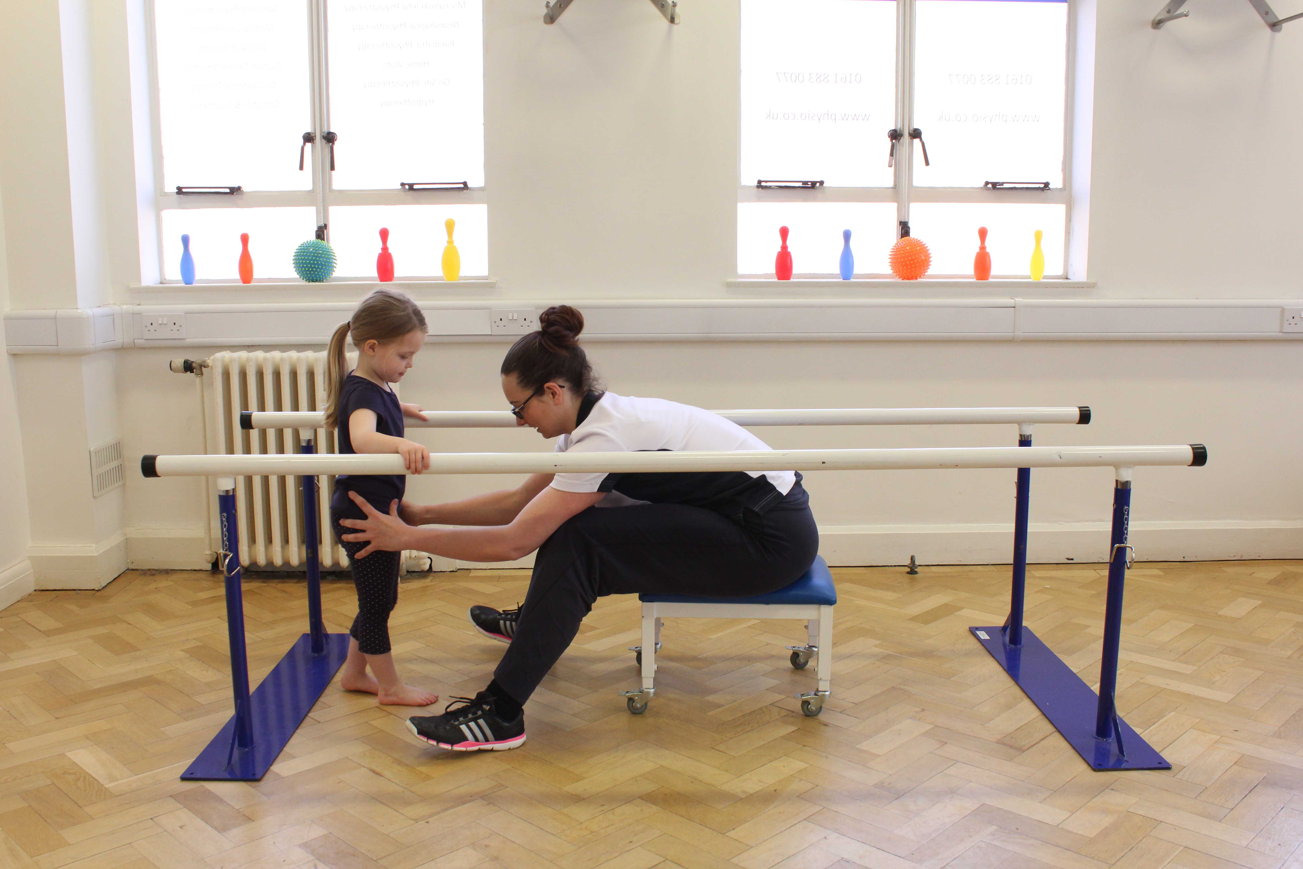 Mobility exercises between the parallel bars supervised by an experienced physiotherapist