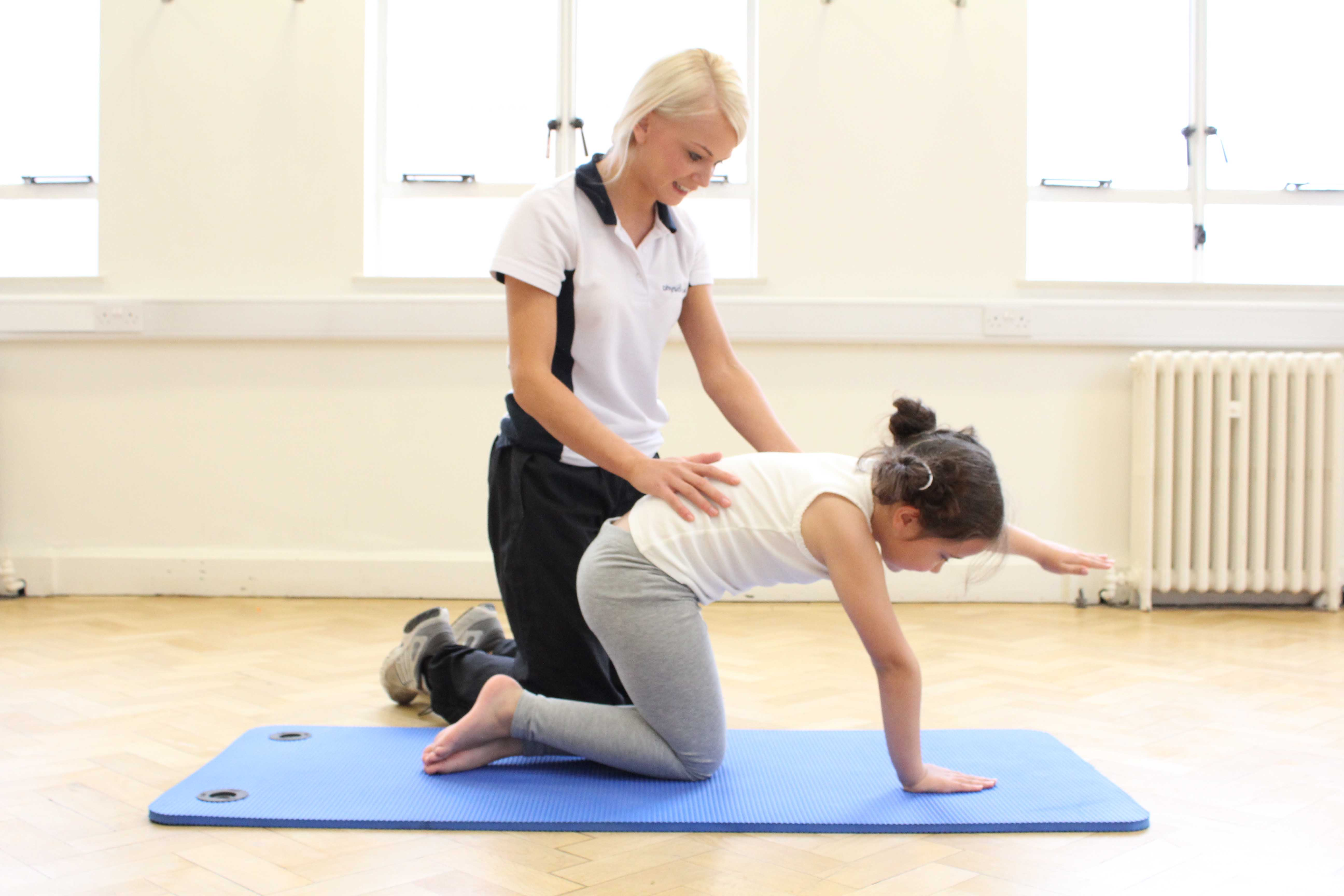 Paediatric physiotherapist supervising mobility exercises to achieve developmental milestones