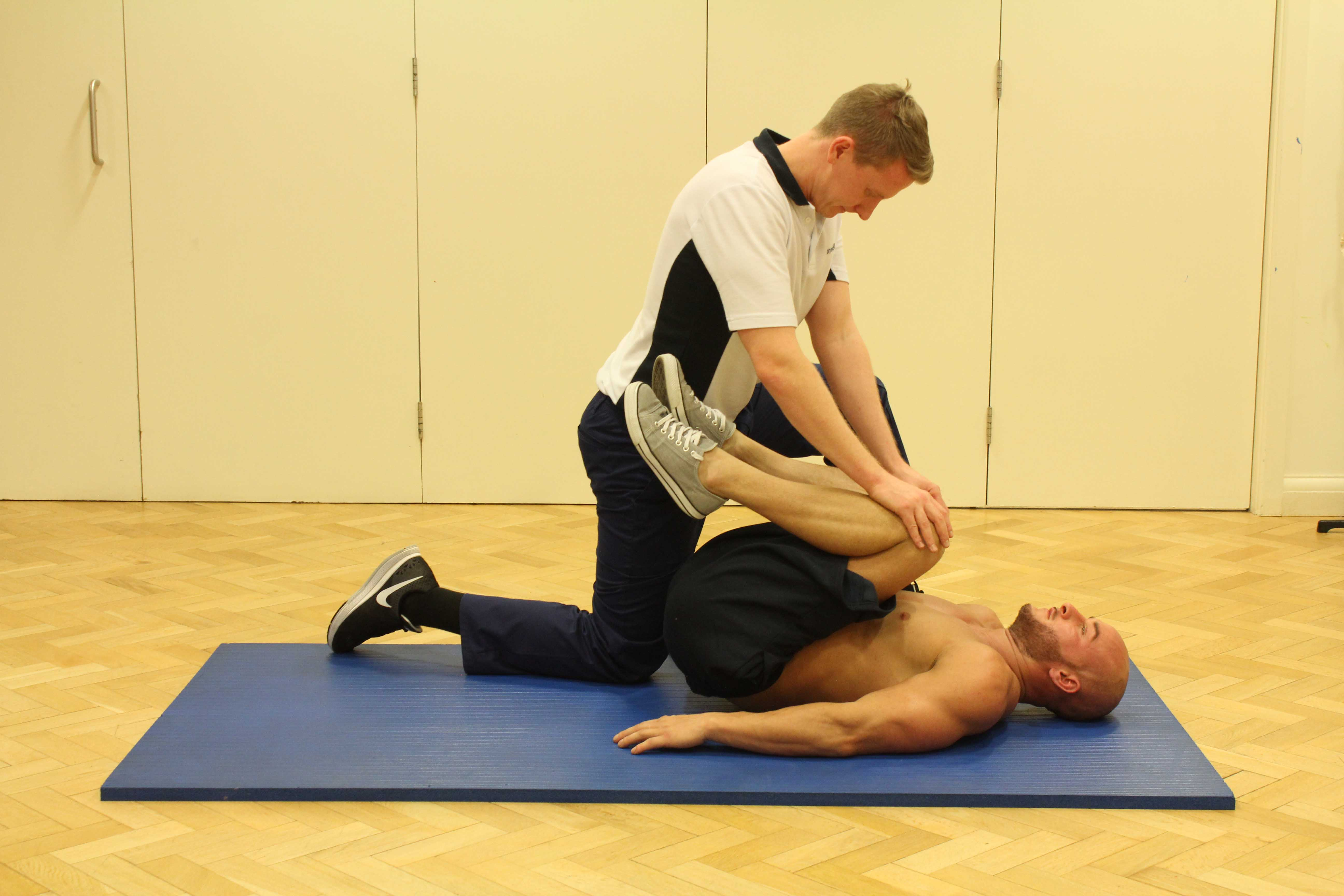 Passive stretch of the lower back muscles performed by MSK physiotherapist