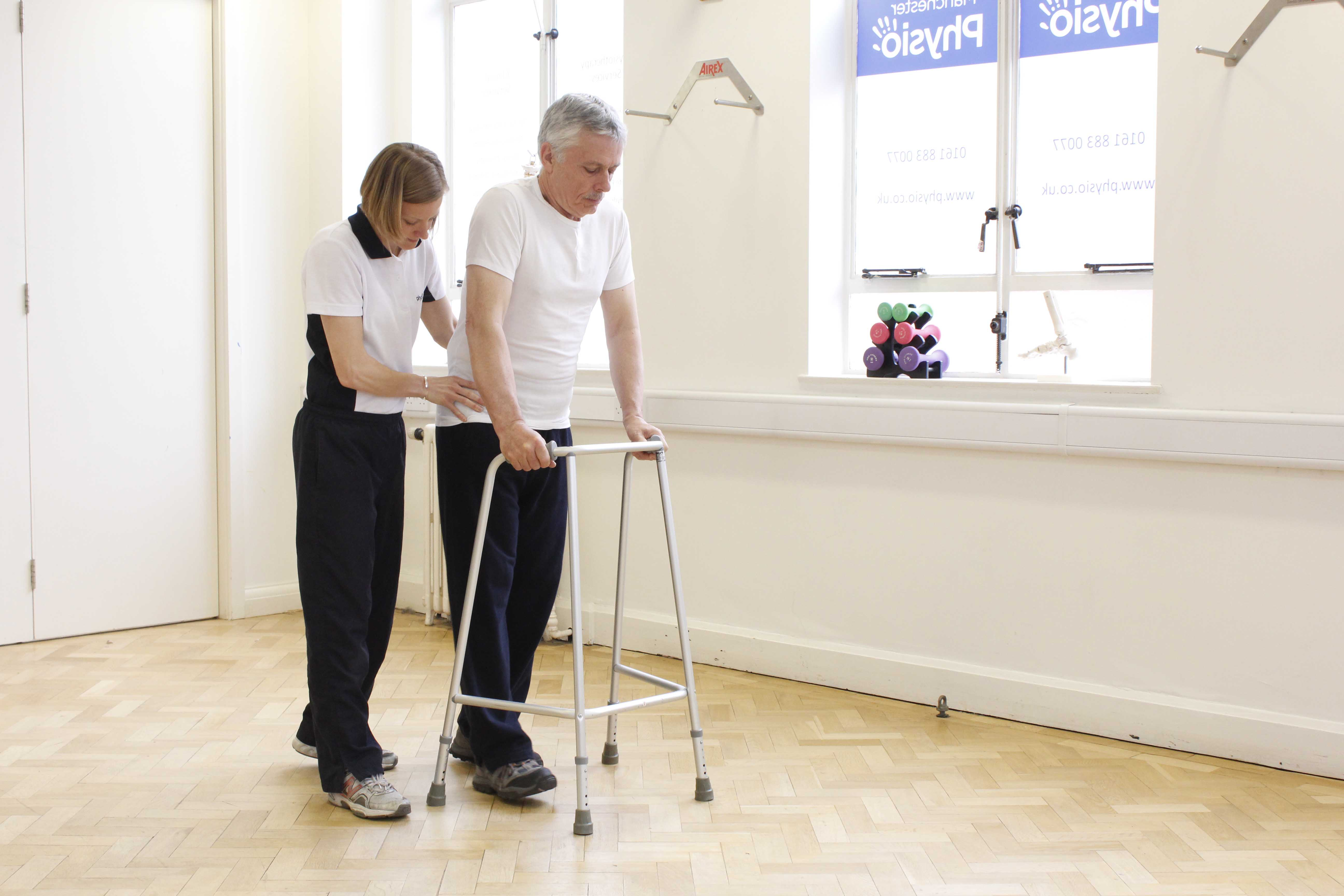 Physiotherapist supervising mobilisation using a walking frame