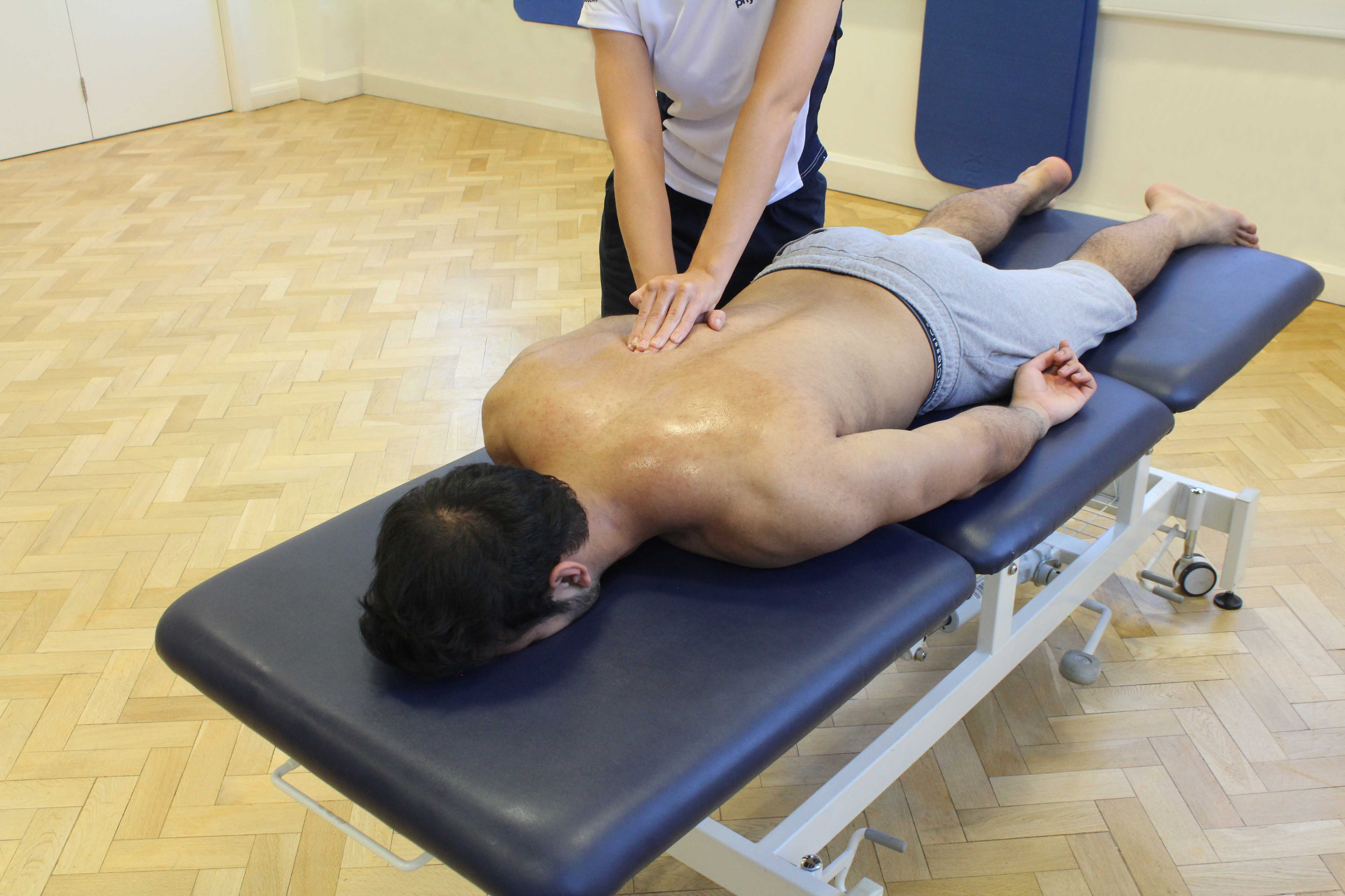 Soft tissue massage of the upper back and trapezius muscles by an experienced physiotherapist