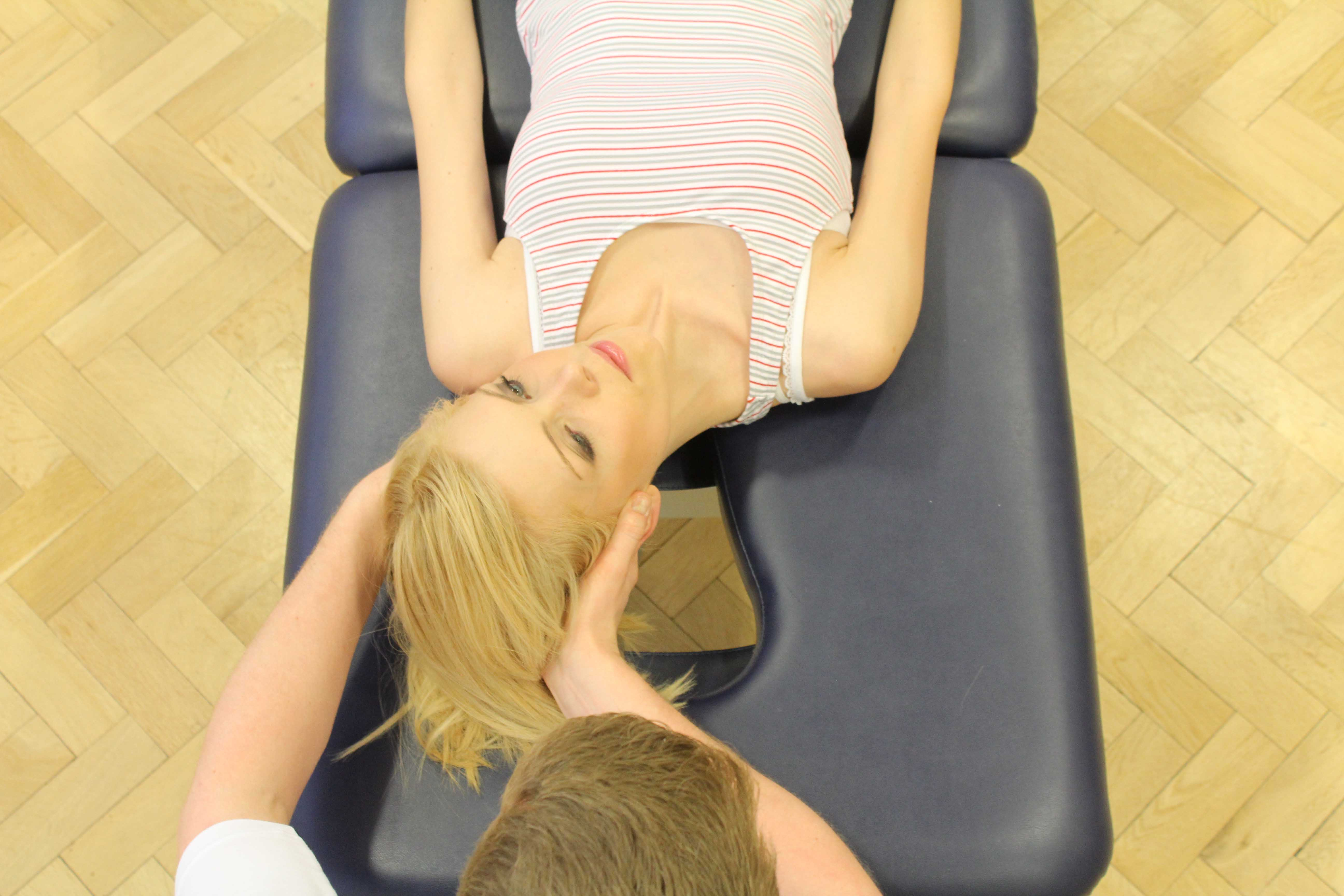 An experienced physiotherapist performing the eply manoeuvre to address vestibular issues