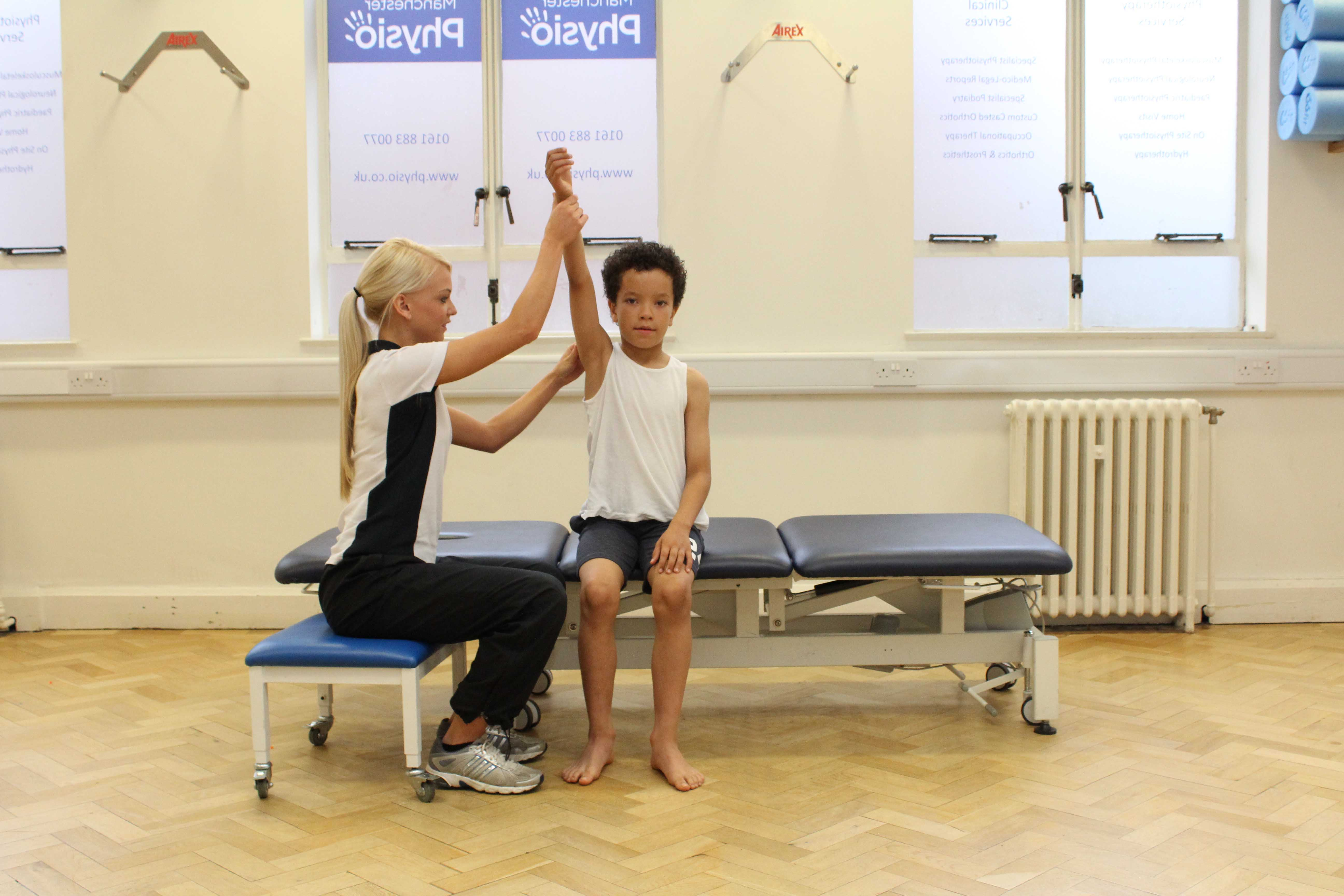 passive mobility and stretch exercises for the arm and shoulder performed by a paediatric neuro physiotherapist