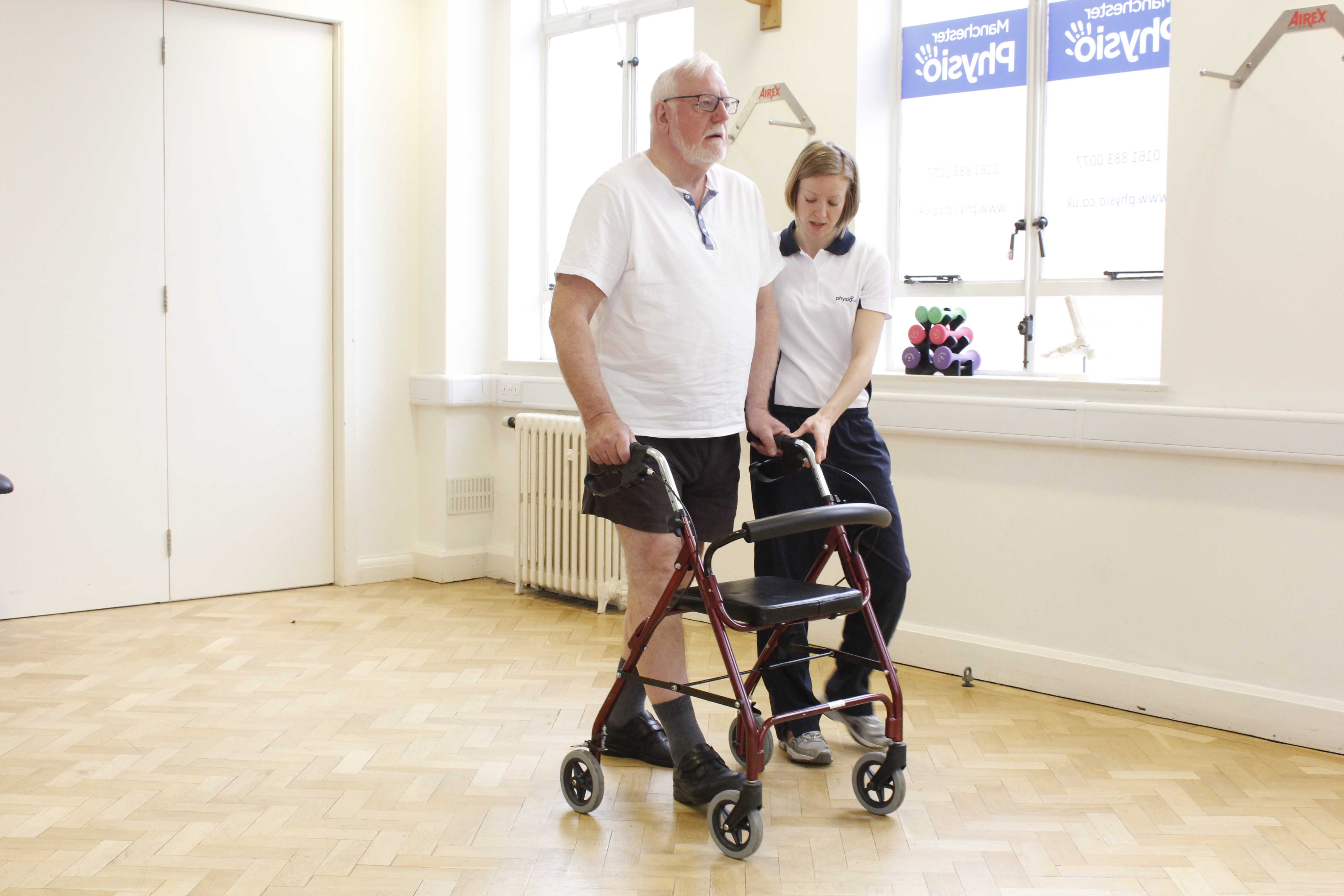 Physiotherapist supervising the use of a wheeled frame to minimise the risk of falls
