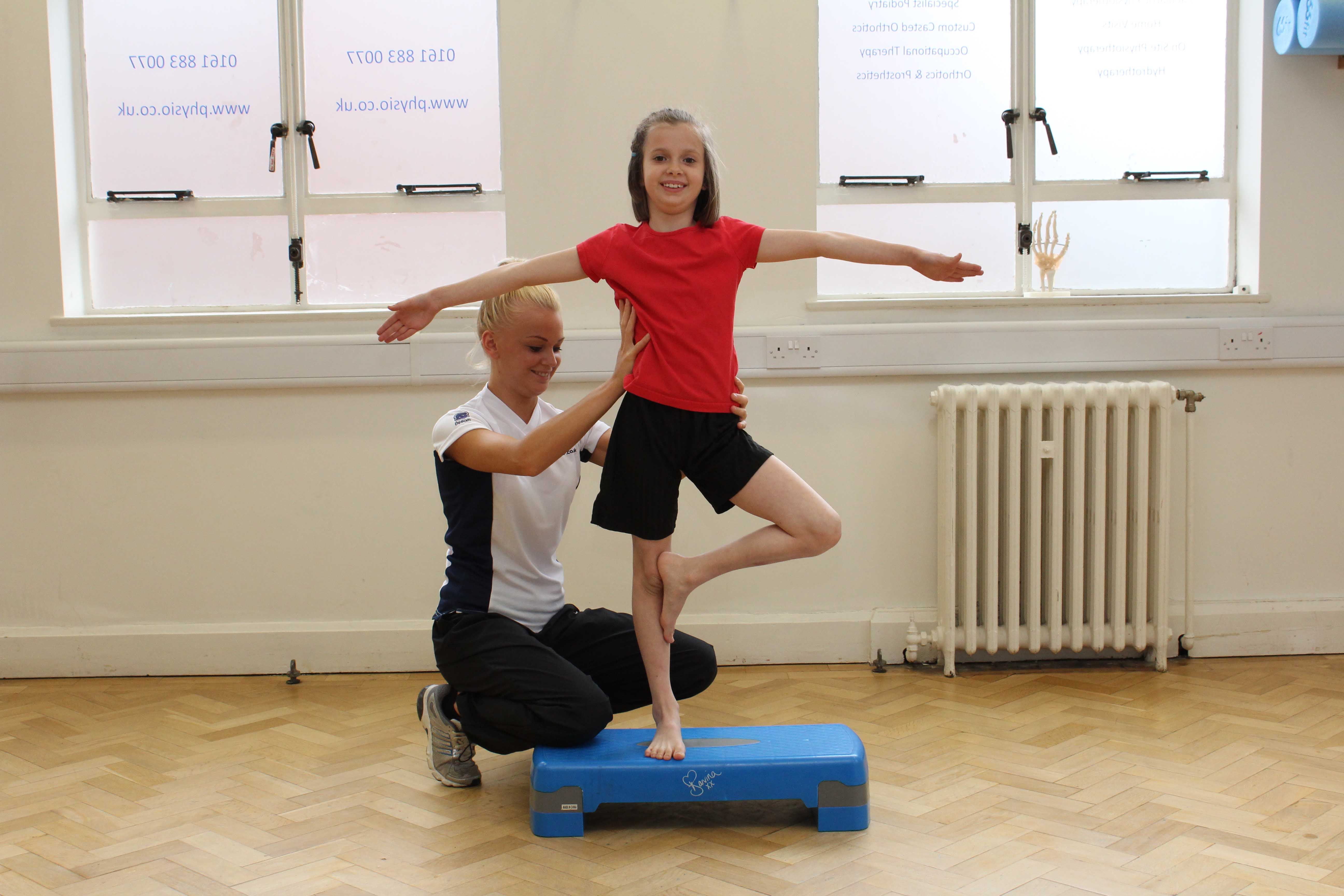 Therapist assists during progressive balance training exercises