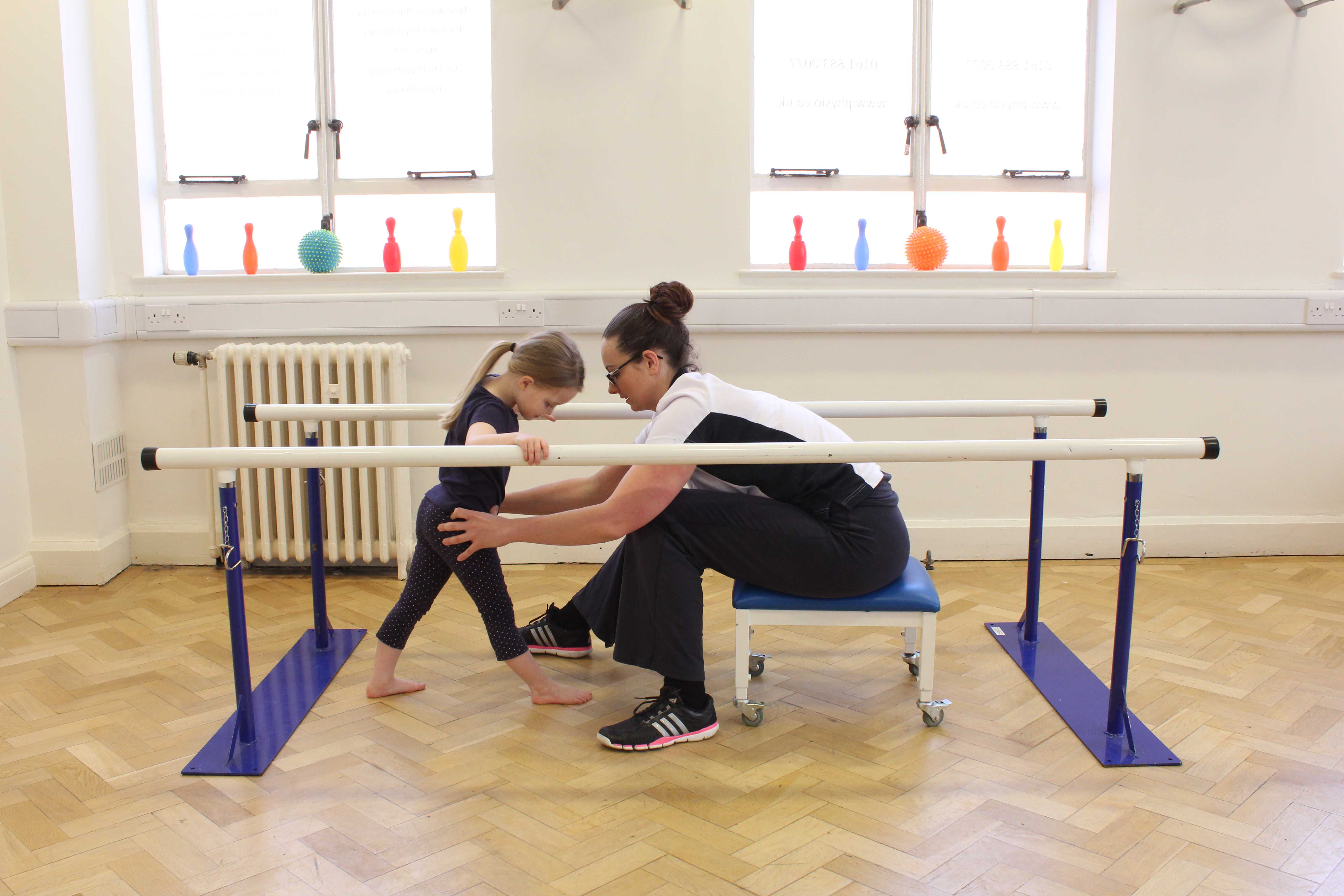 Mobility exercises assisted by the physiotherapist between the parallel bars