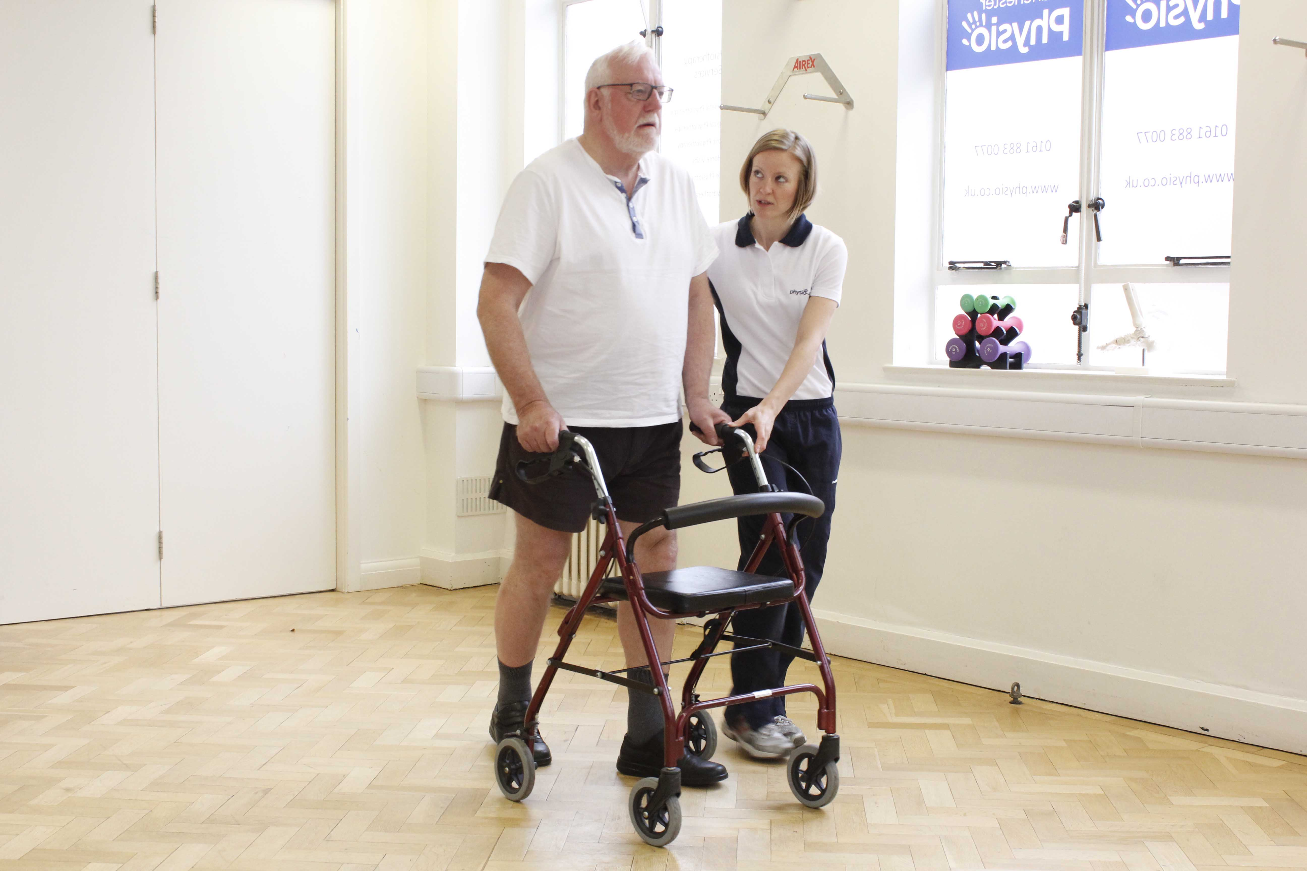 Mobility exercises using a rolator frame and close supervision of a physiotherapist