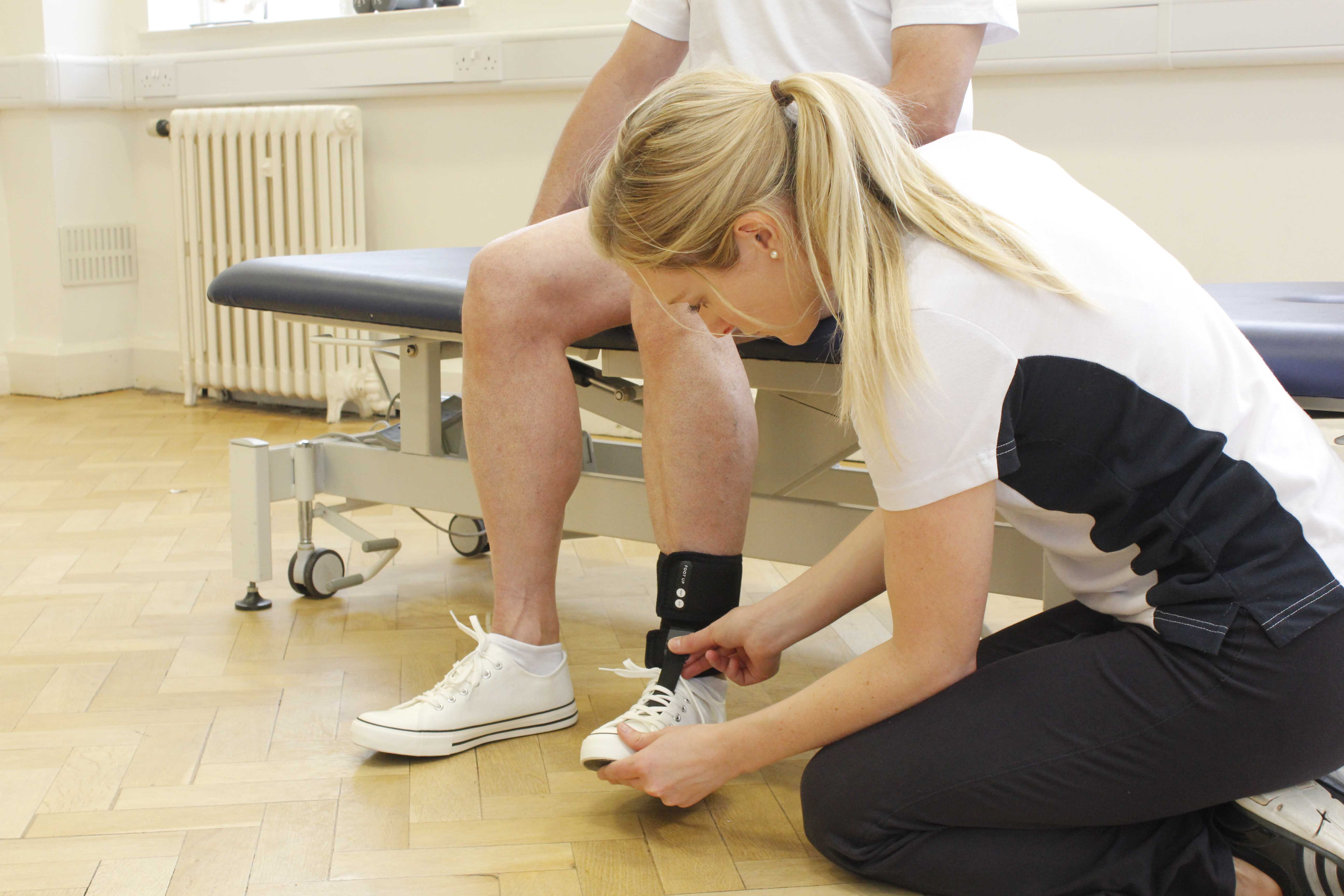 Neurological physiotherapist fitting an ankle brace to prevent foot drop during mobilisation.