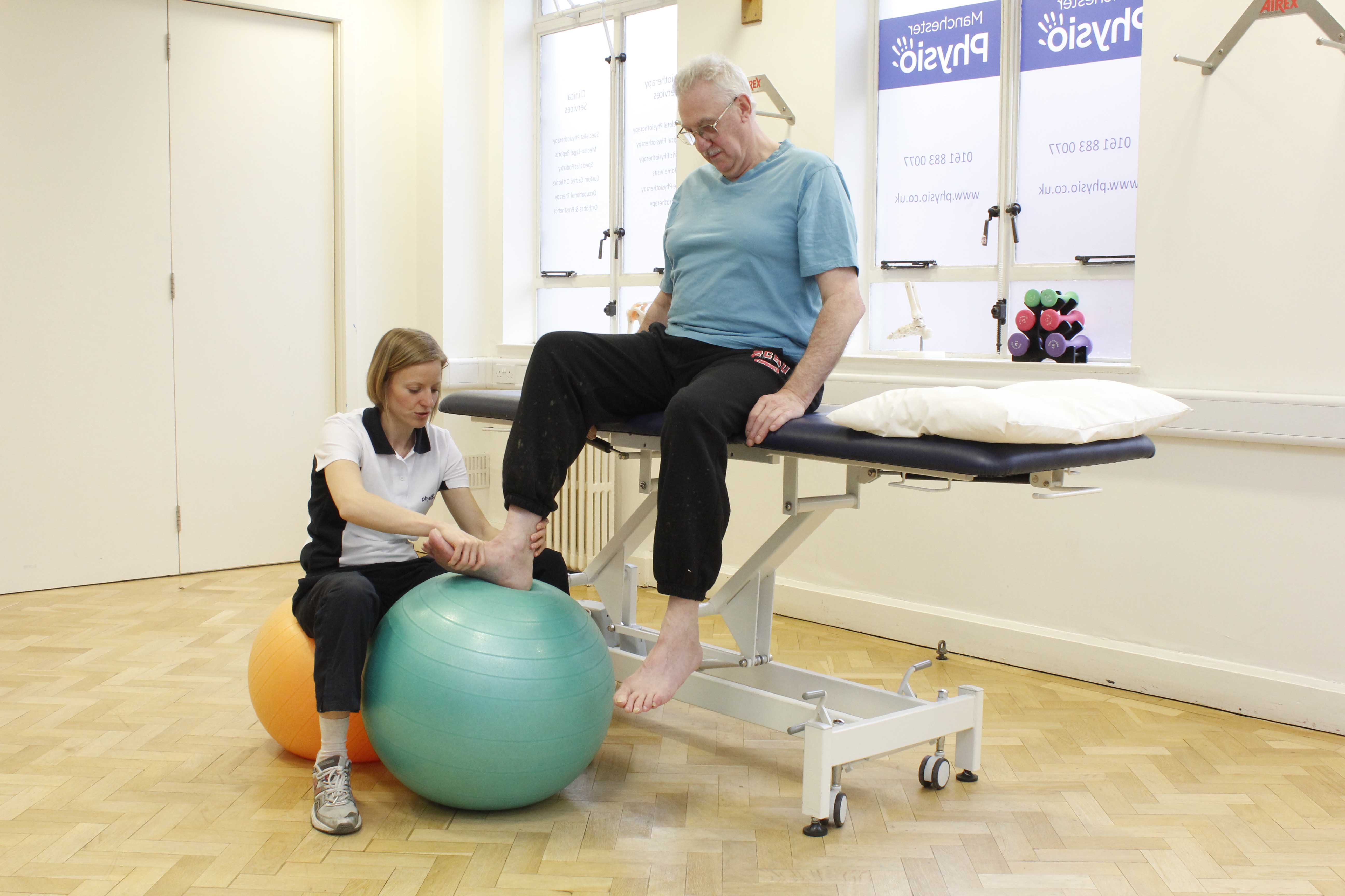 Experienced physiotherapist assisting with some ankle dorsiflexion exercises