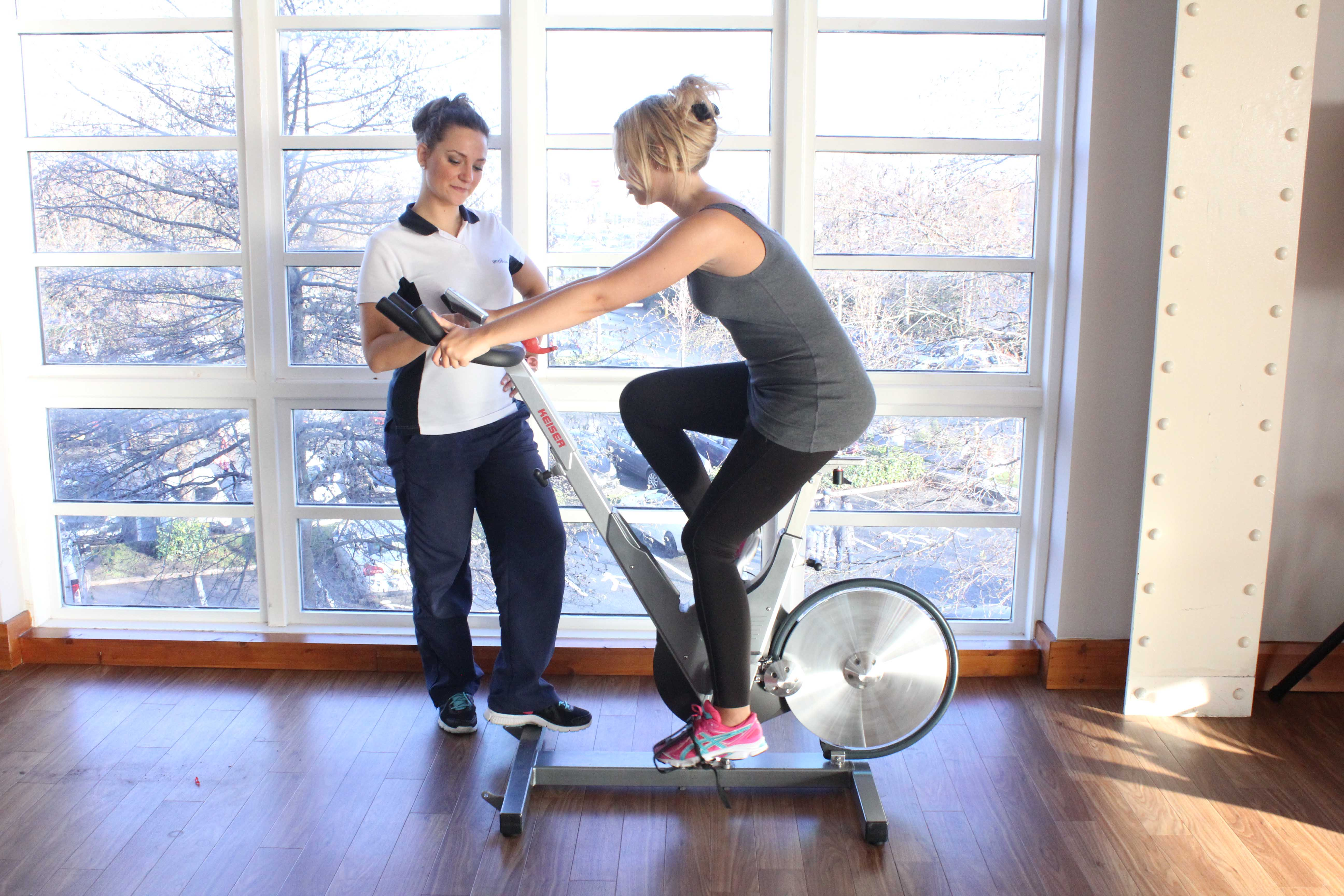 Leg strengthening exercises on a bike supervised by an experienced physiotherapist