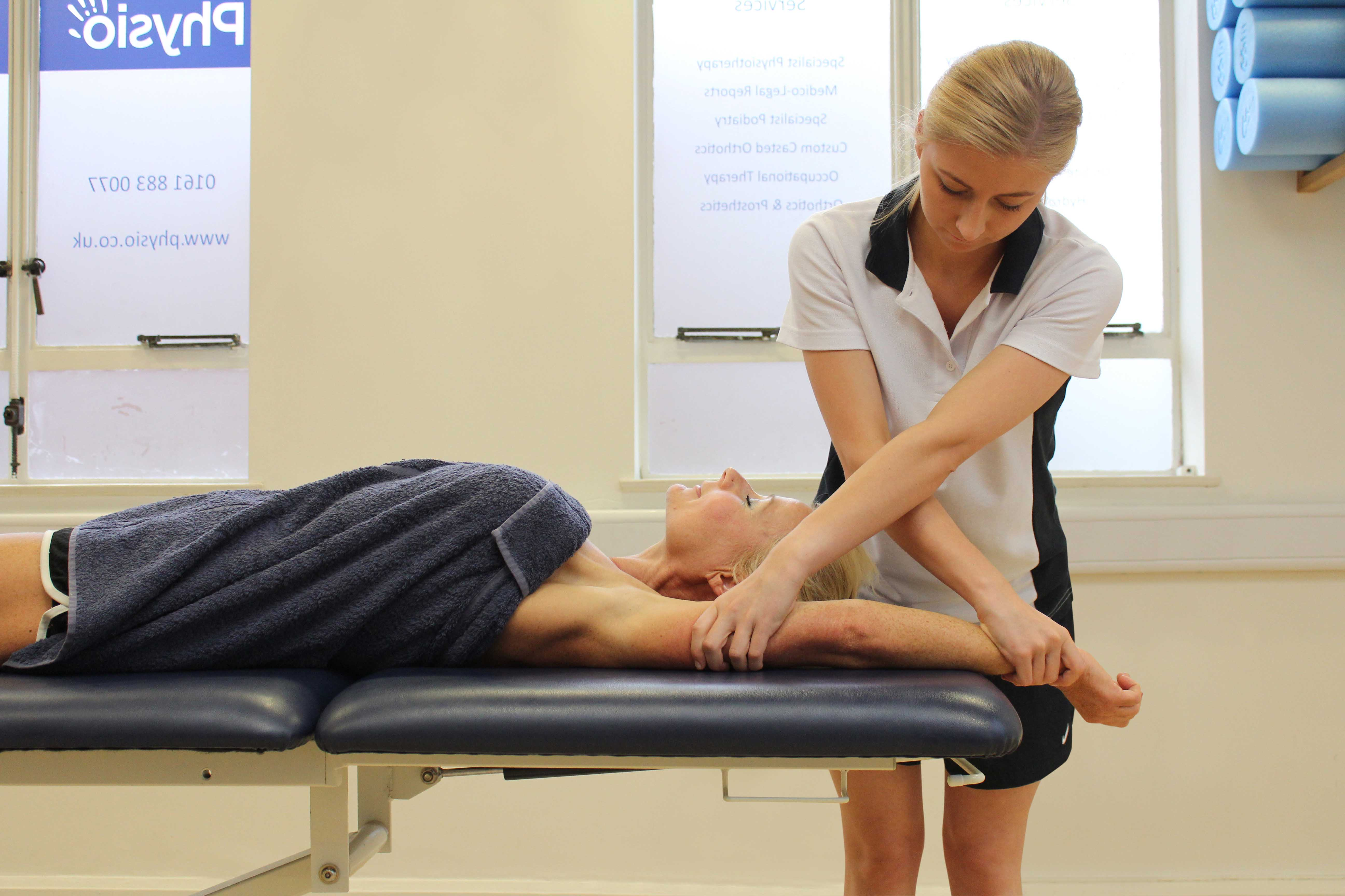 Soft tissue massage and stretch of the muscle and connective tissues around the elbow