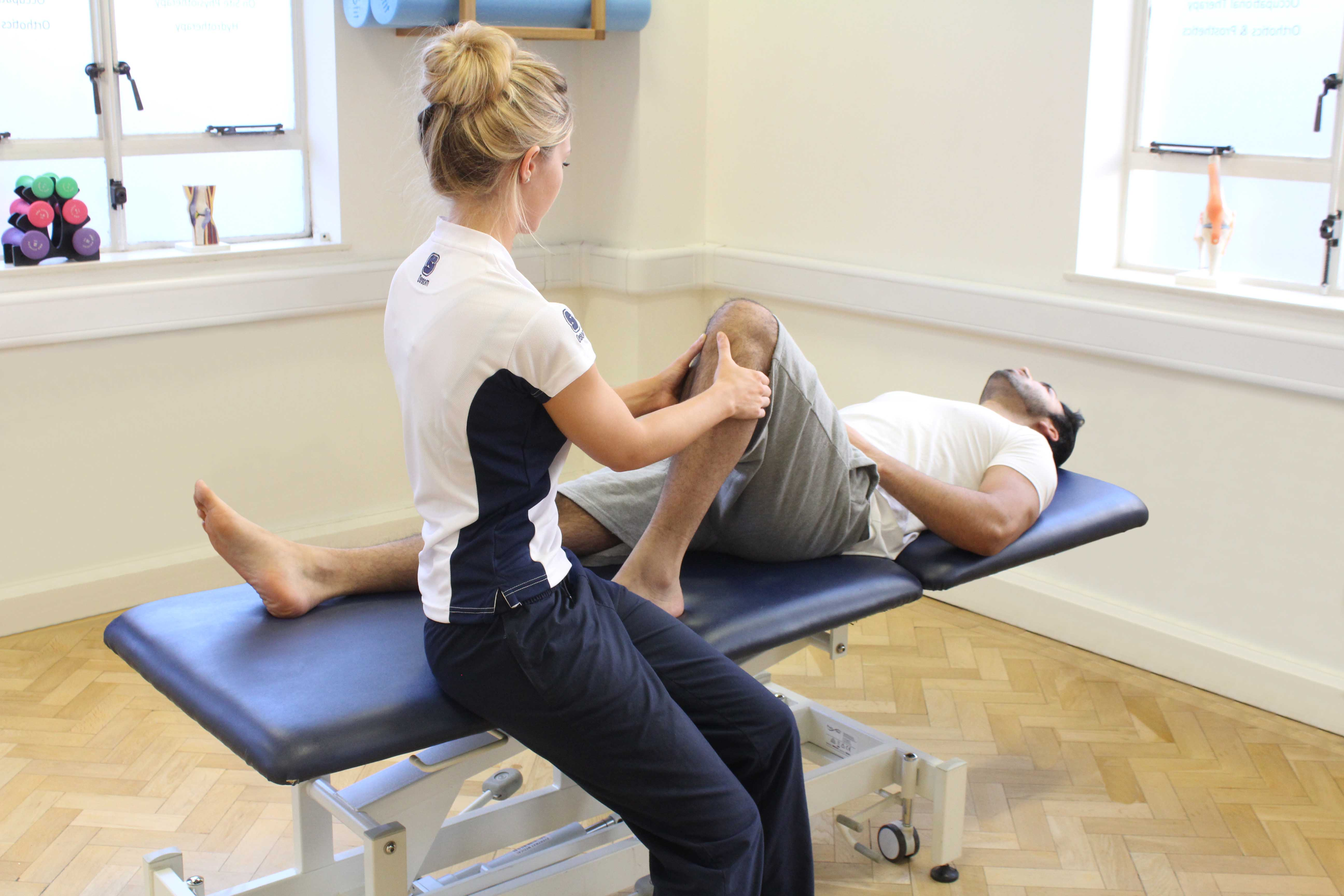 Therapist performing knee assessment