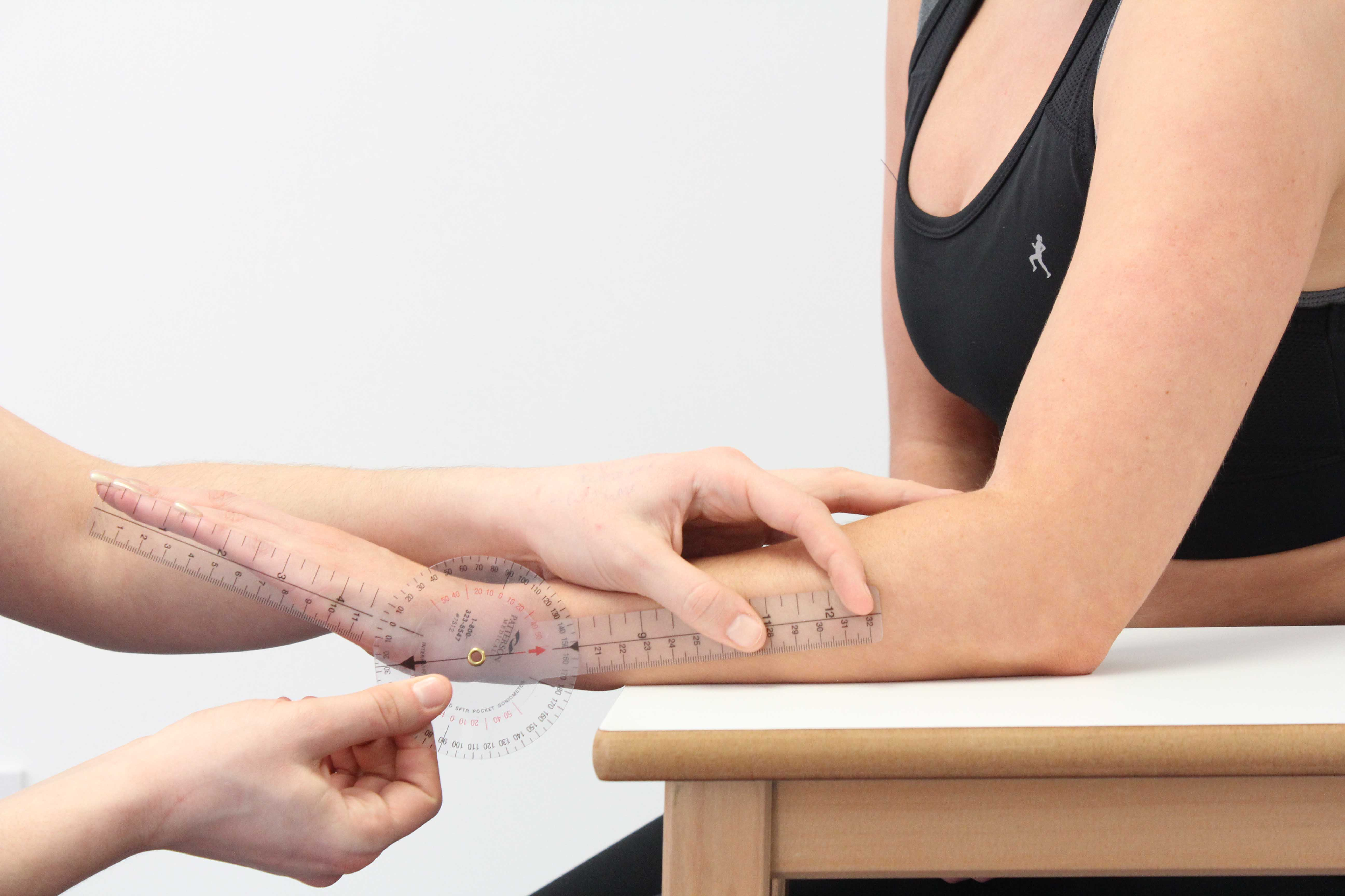 Therapist measuring wrist extension using a goniometer
