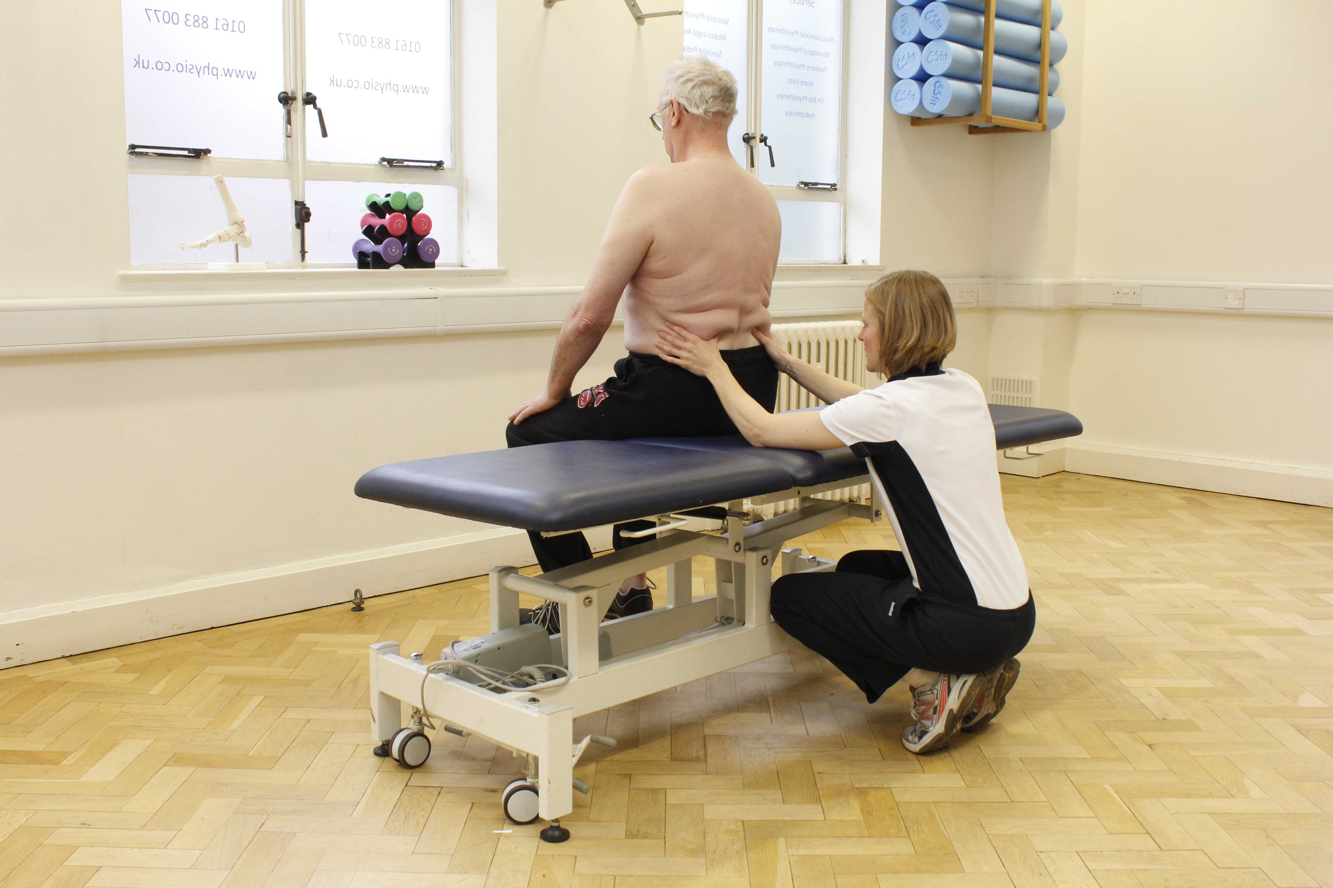 Neurological physiotherapist using passive stretches and mobilisations of the hip, knee and ankle to relieve stiffness