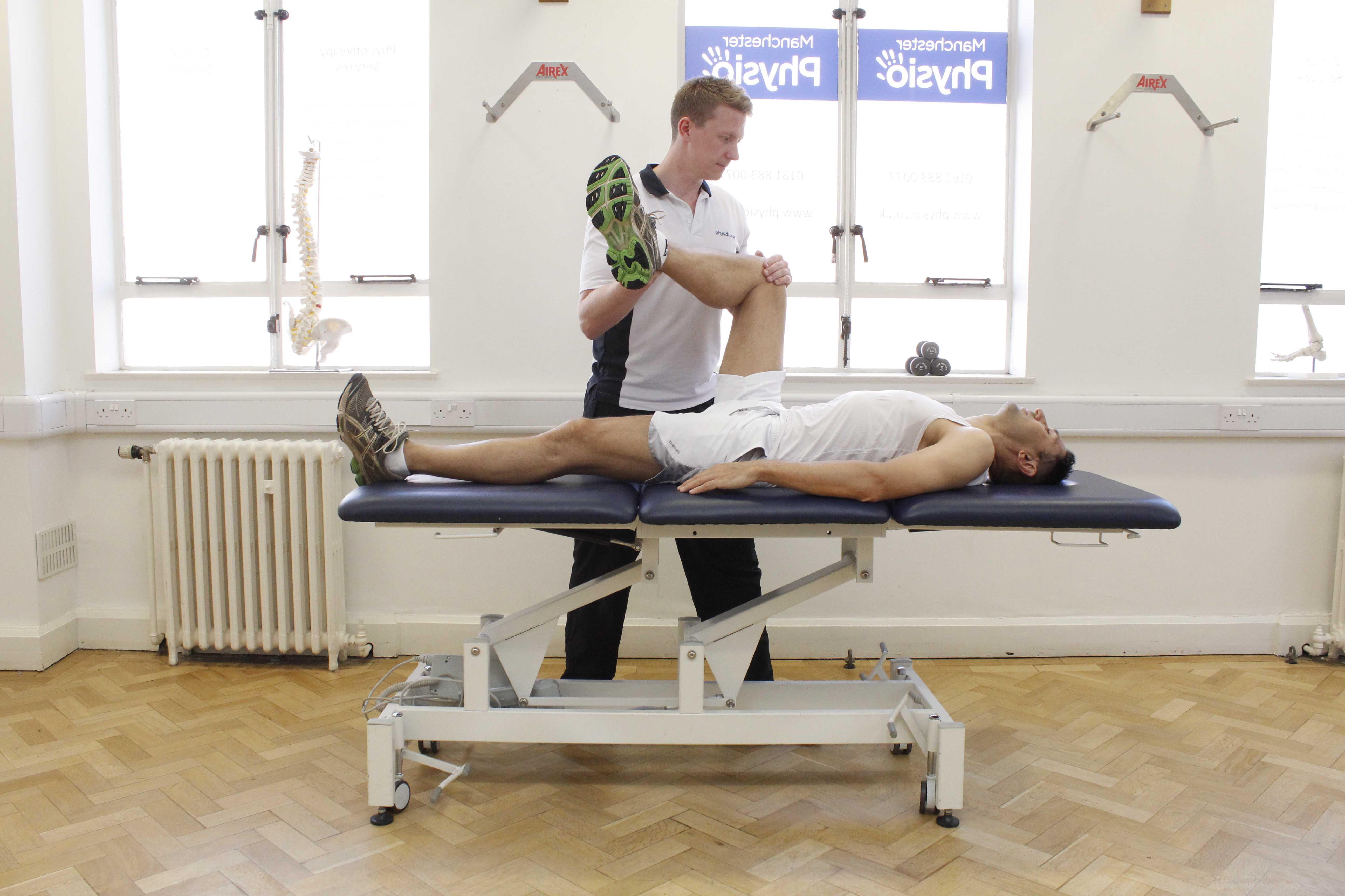 Experienced physiotherapist performing hip and knee stretches and mobilisations to reduce pain and muscle tone.