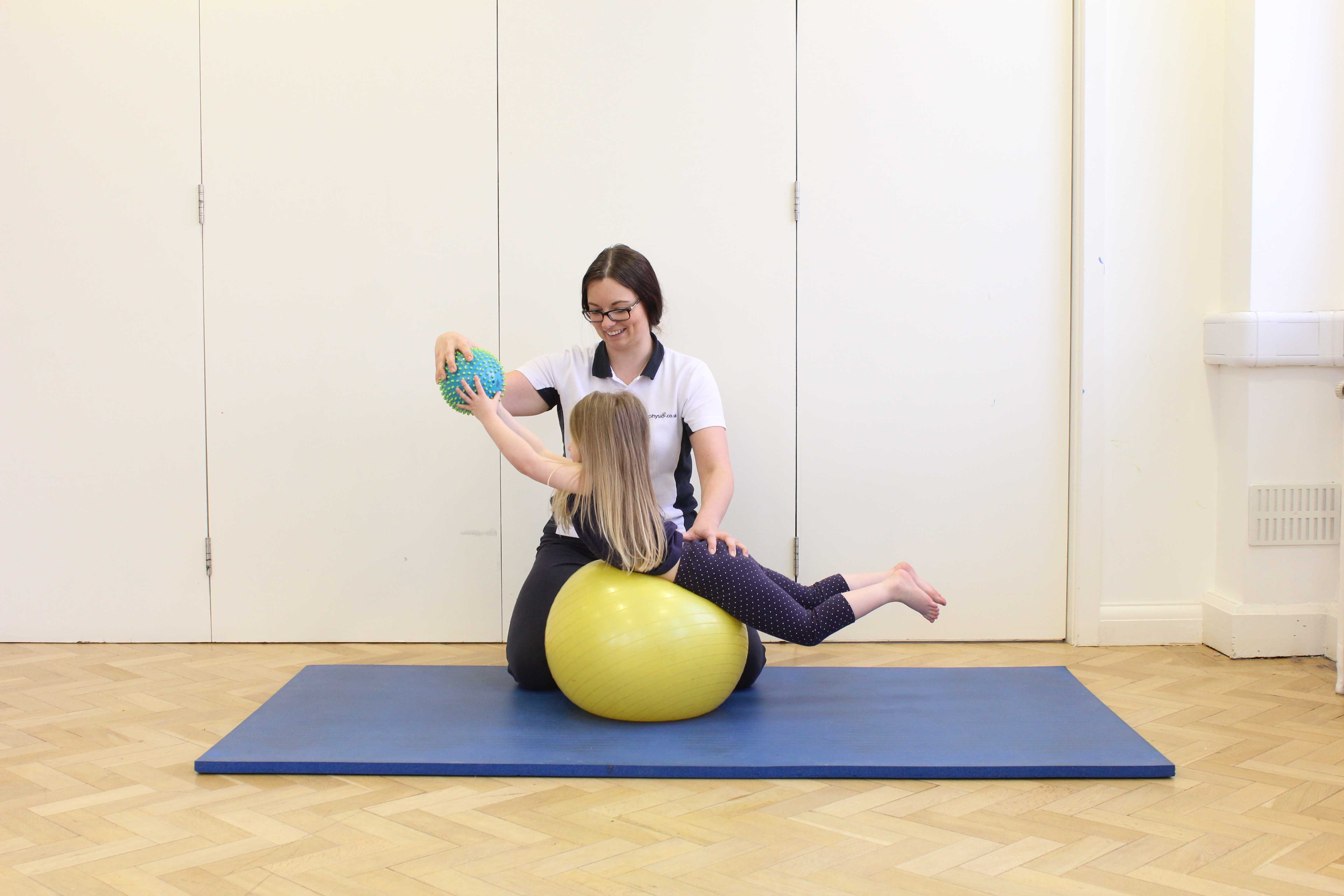 Stretching and toning exercises assisted by a paediatric physiotherapist