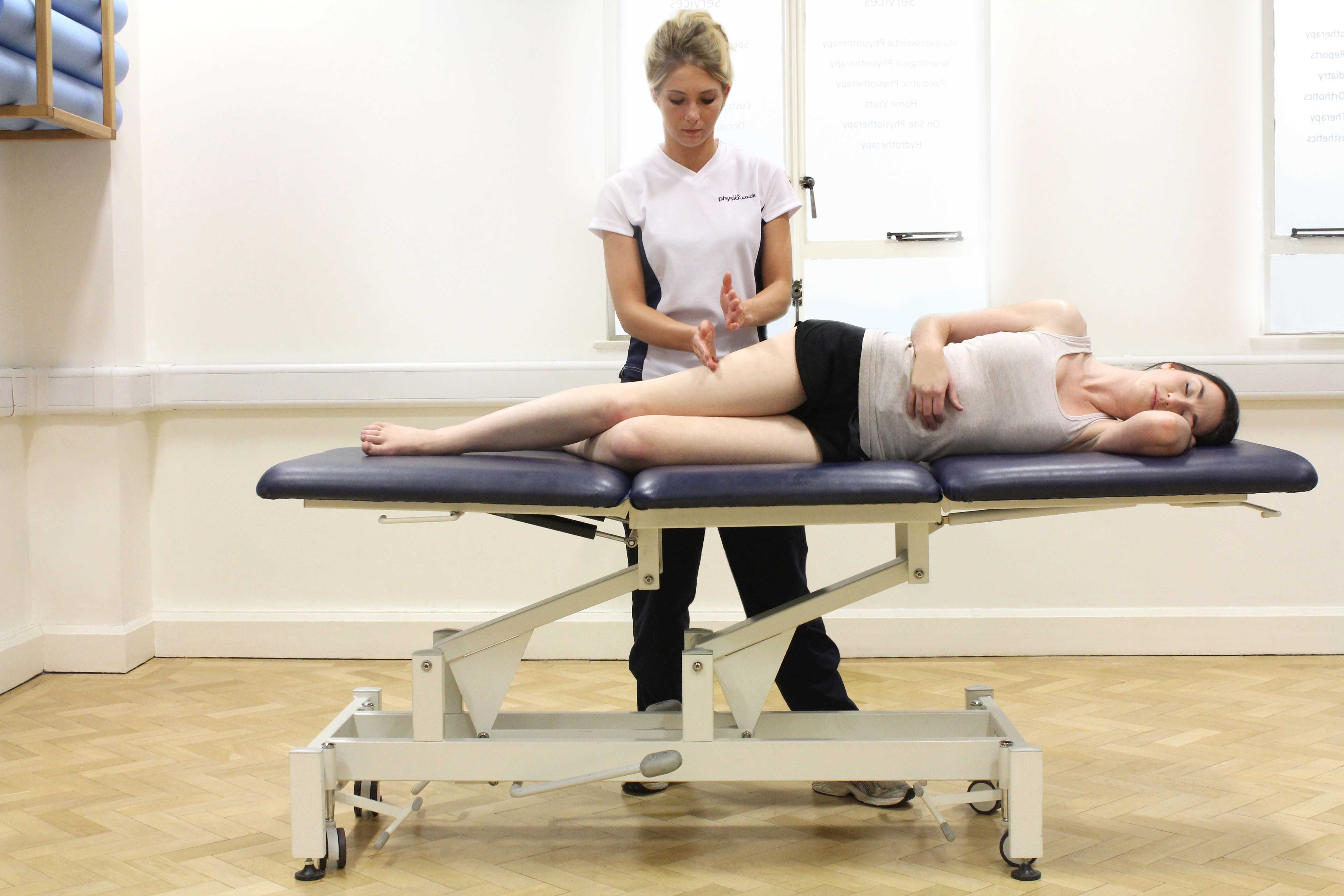 Hacking percussion massage of the IT band and vastus lateralis muscle by a specialist MSK therapist