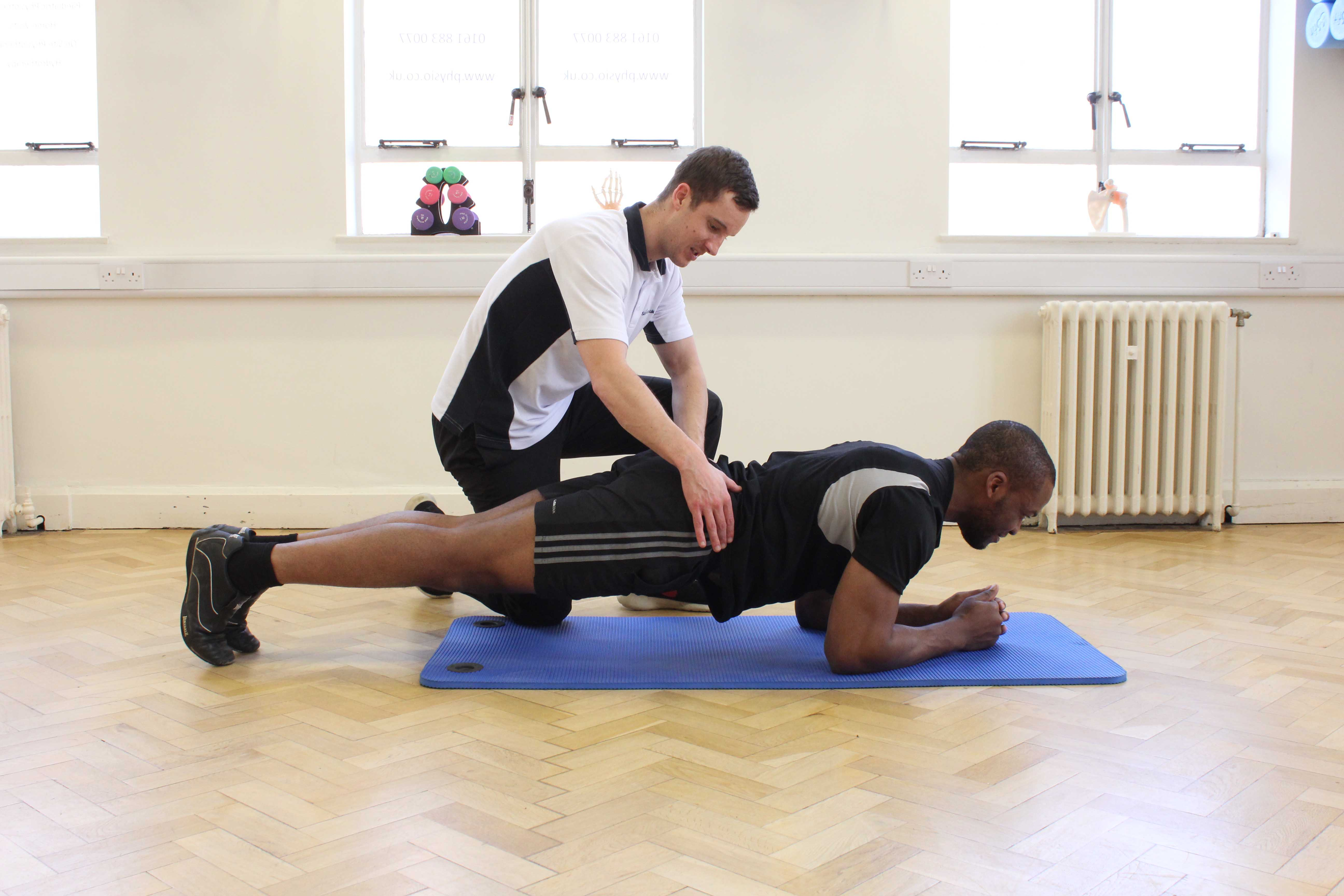 Planking toning exercises for the back supervised by an experienced physiotherapist