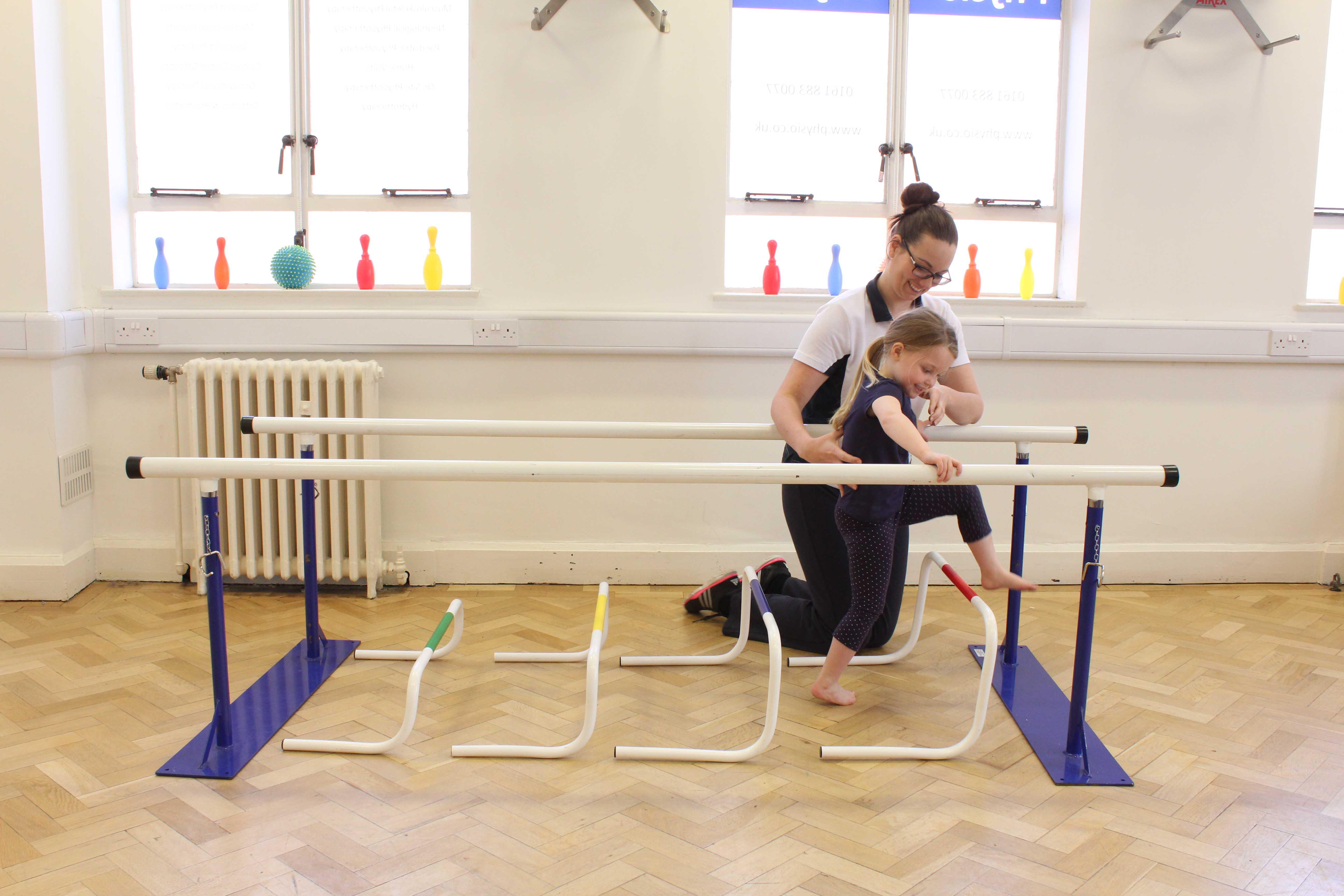 Paediatric neuro physiotherapist supervising mobility exercises between the parallel bars