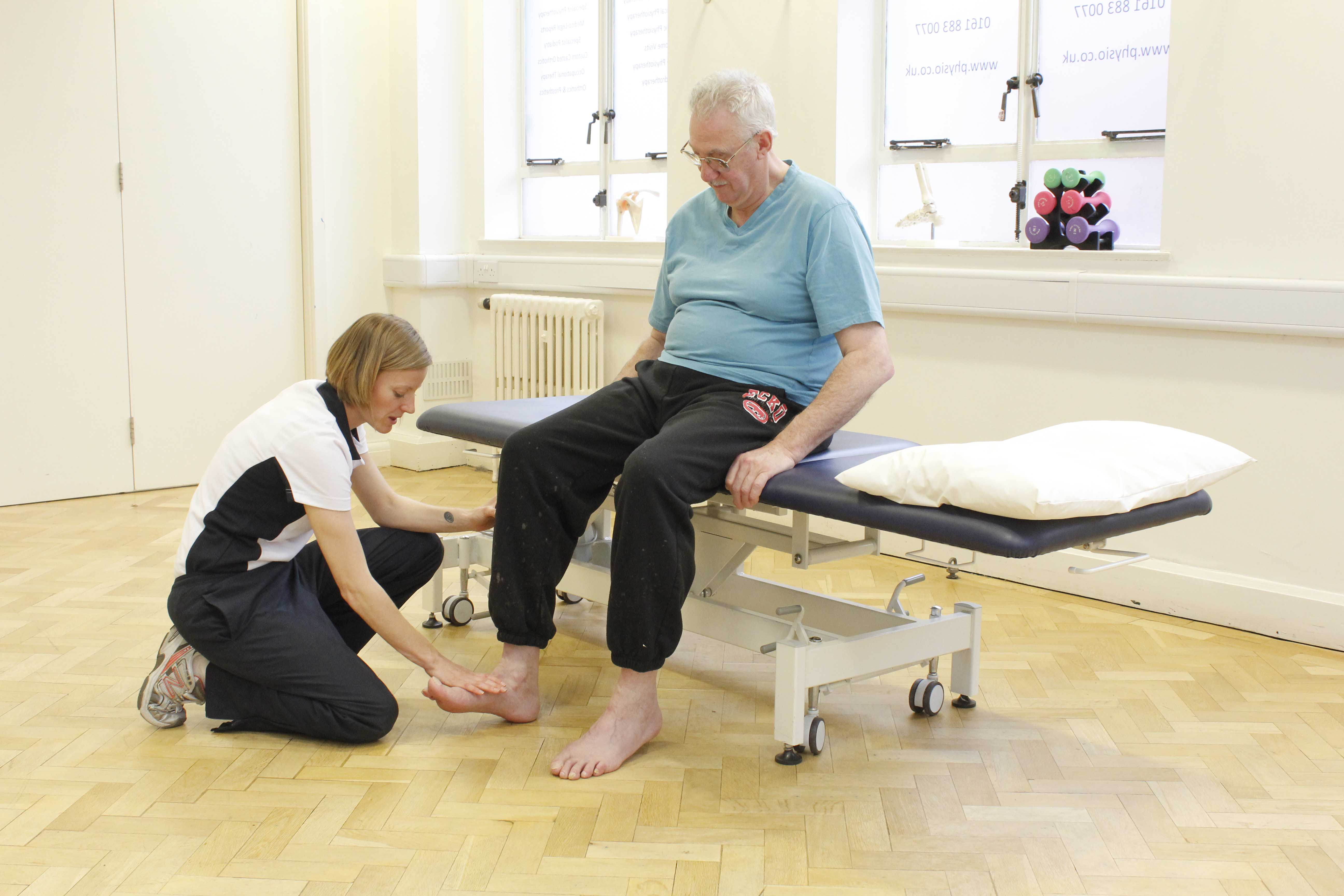 Experienced Physiotherapist assessing ankle mobility and stability