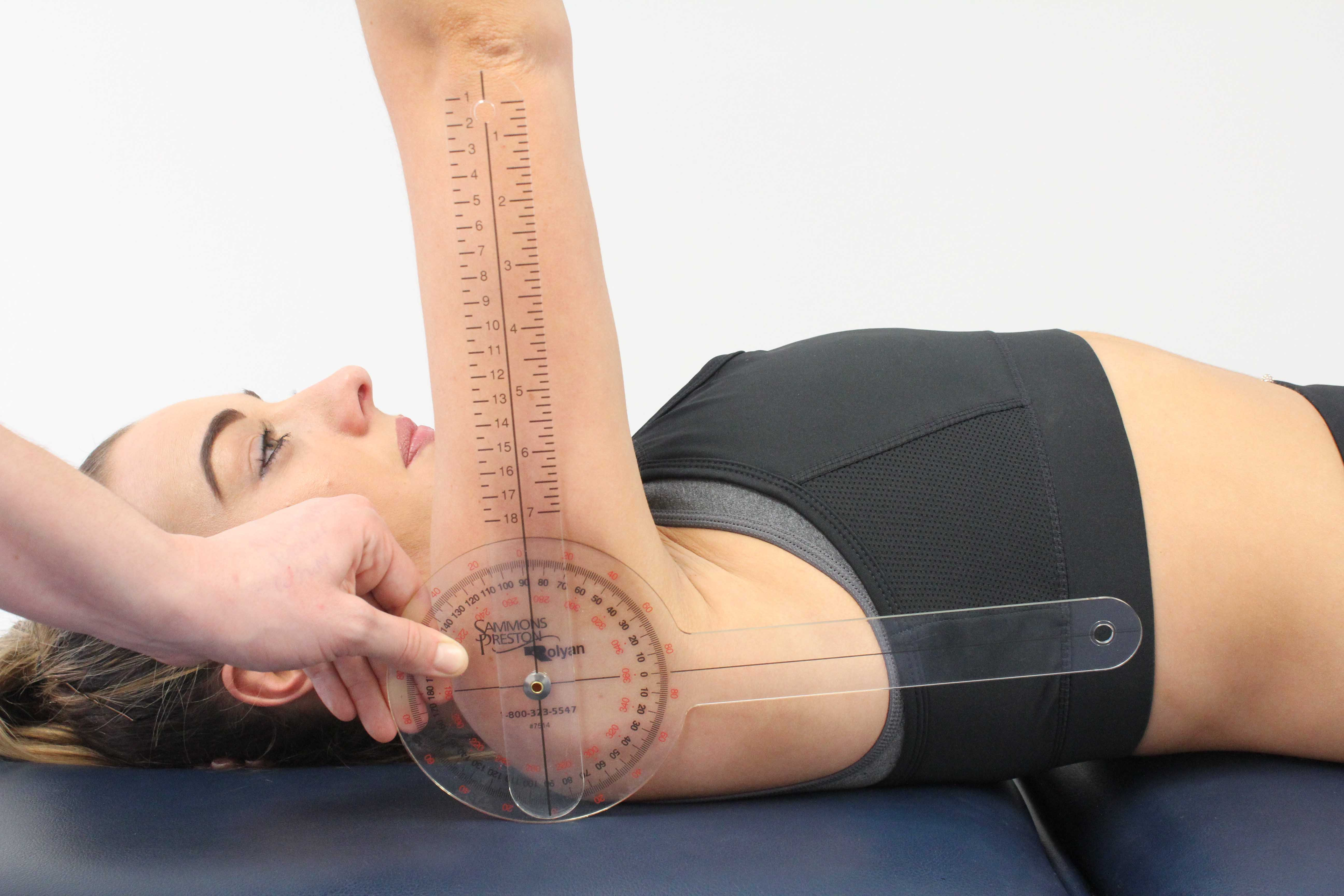 Physiotherapist measuring available range of movement at the shoulder using a goniometer