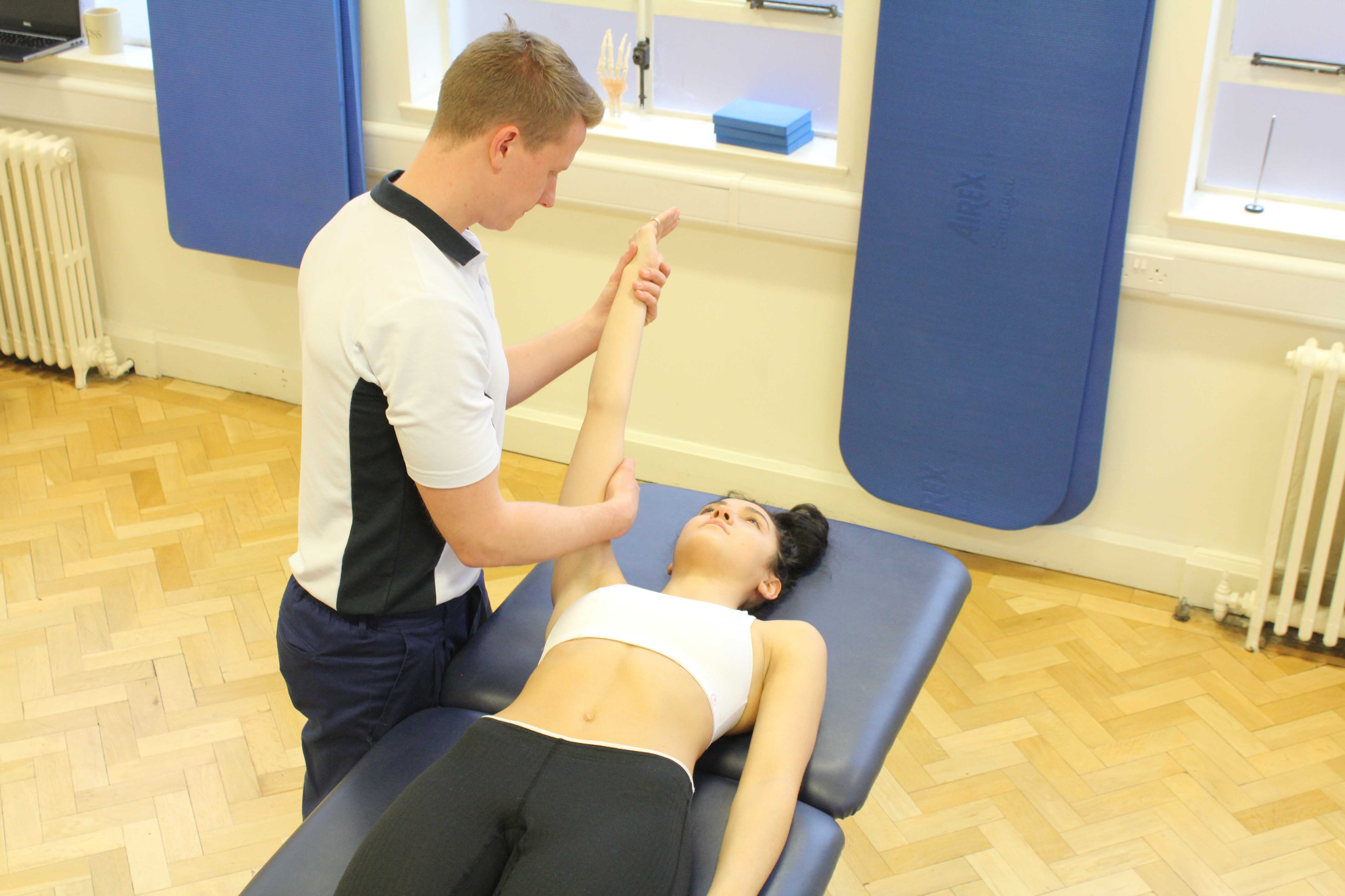 Experienced musculoskeletal physiotherapist assessing a limitation in shoulder movement