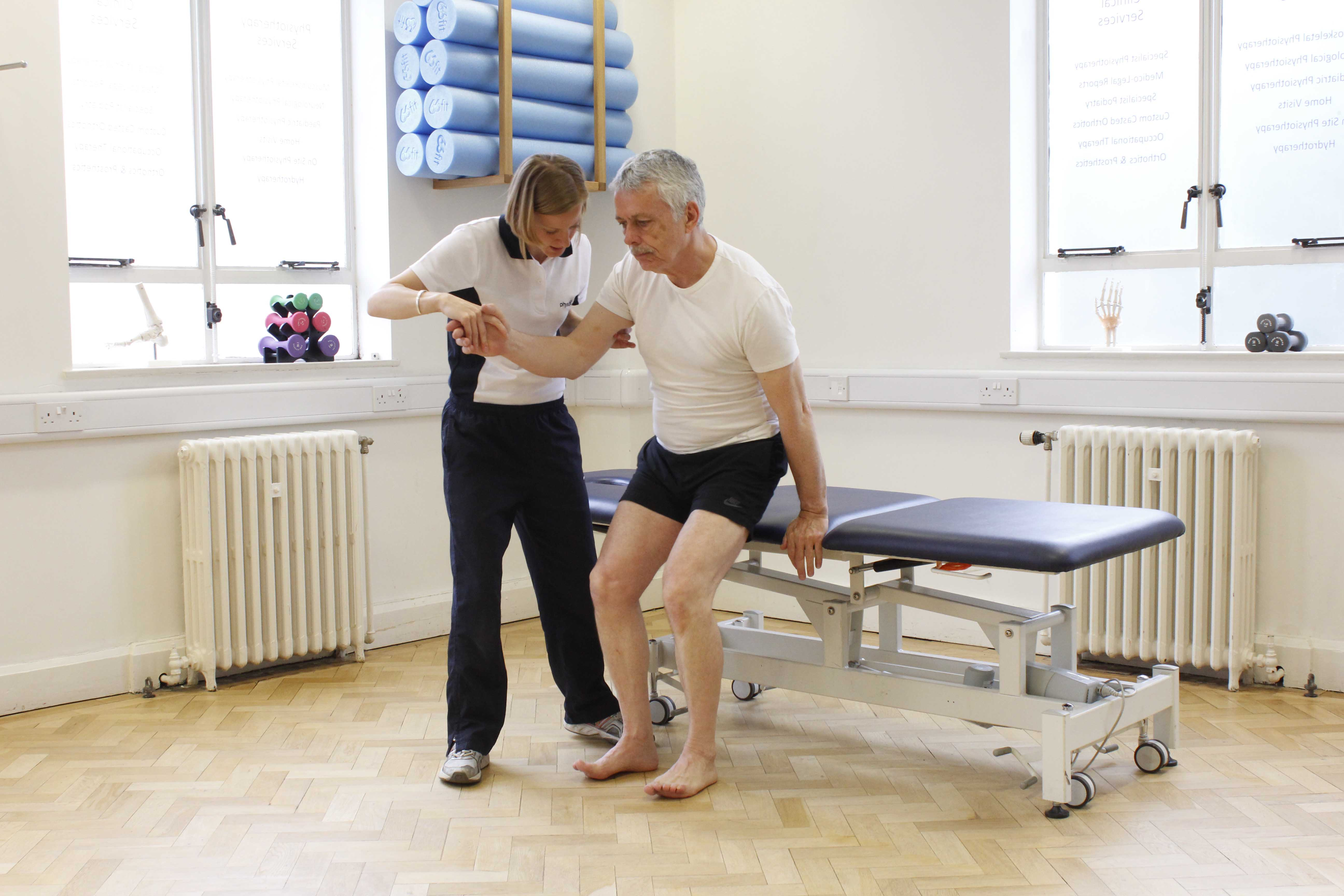 Neurological physiotherapist facilitating client transfers from stitting to standing