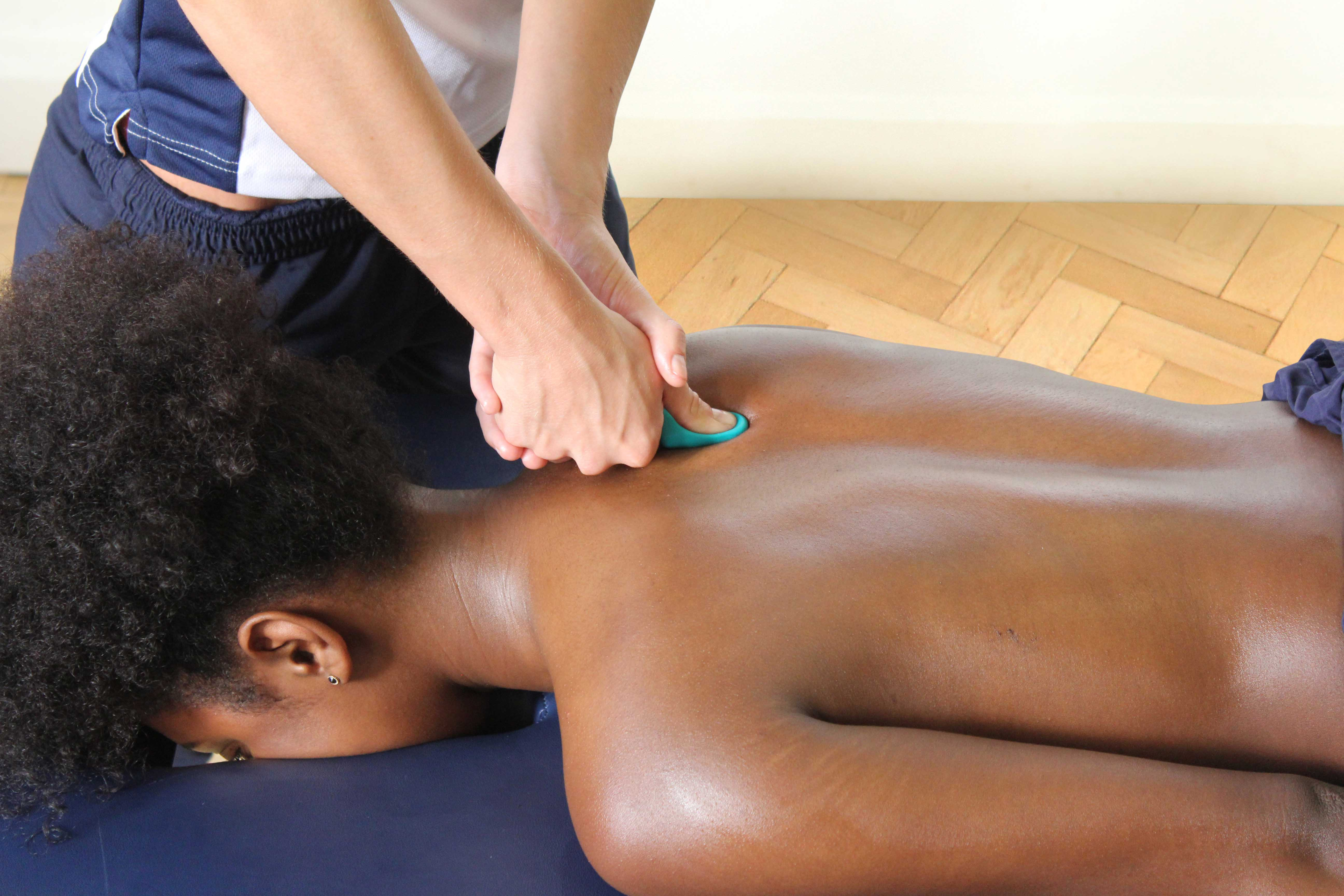 Trigger point massage of the muscles in the upper back using a therapy aid