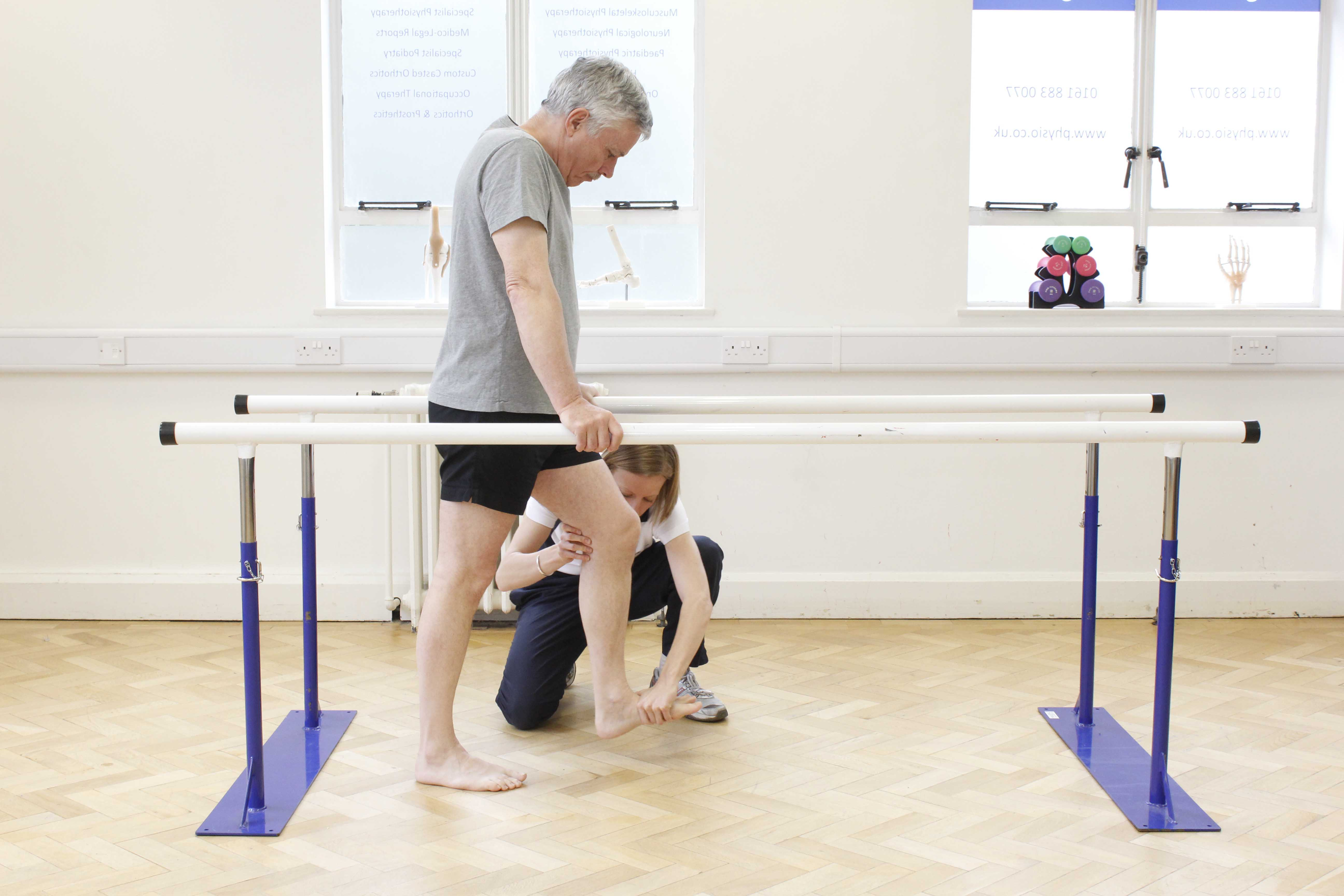 Neurological physiotherapist assisting mobilisation exercises between the parallel bars