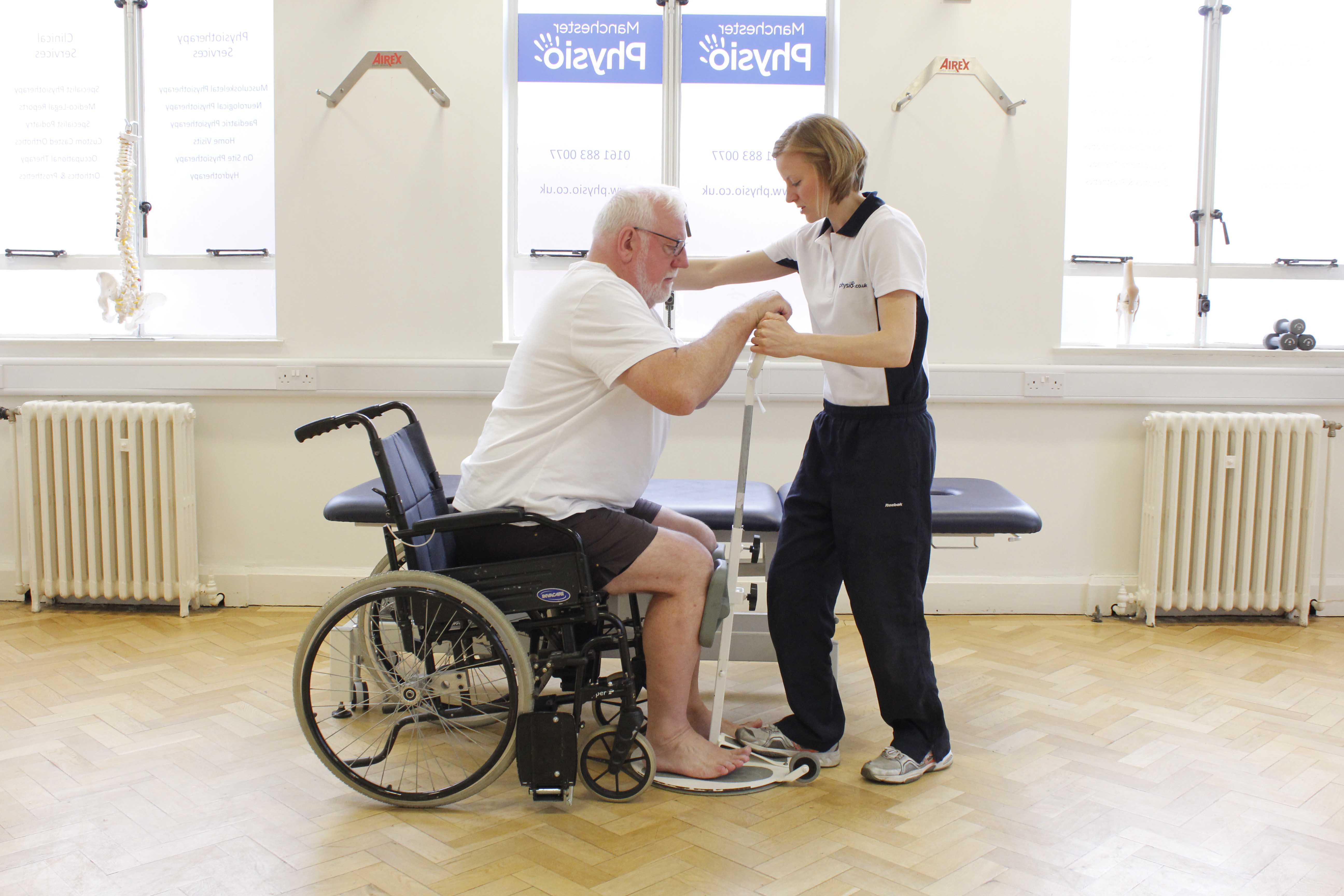 Neurological physiotherapist assisting mobility transfers using a pivot standing frame