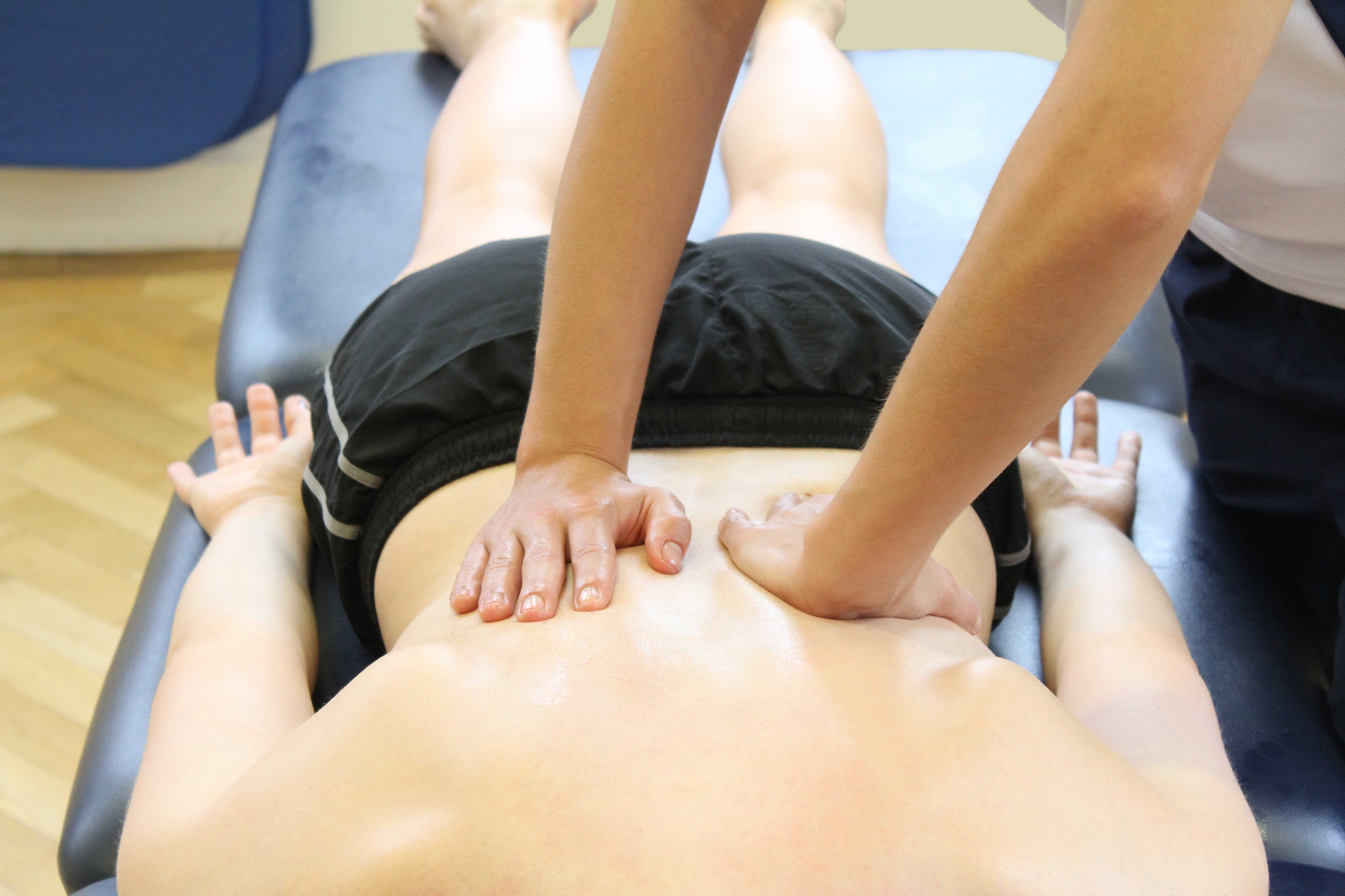 Therapist applying compression massage to lower back