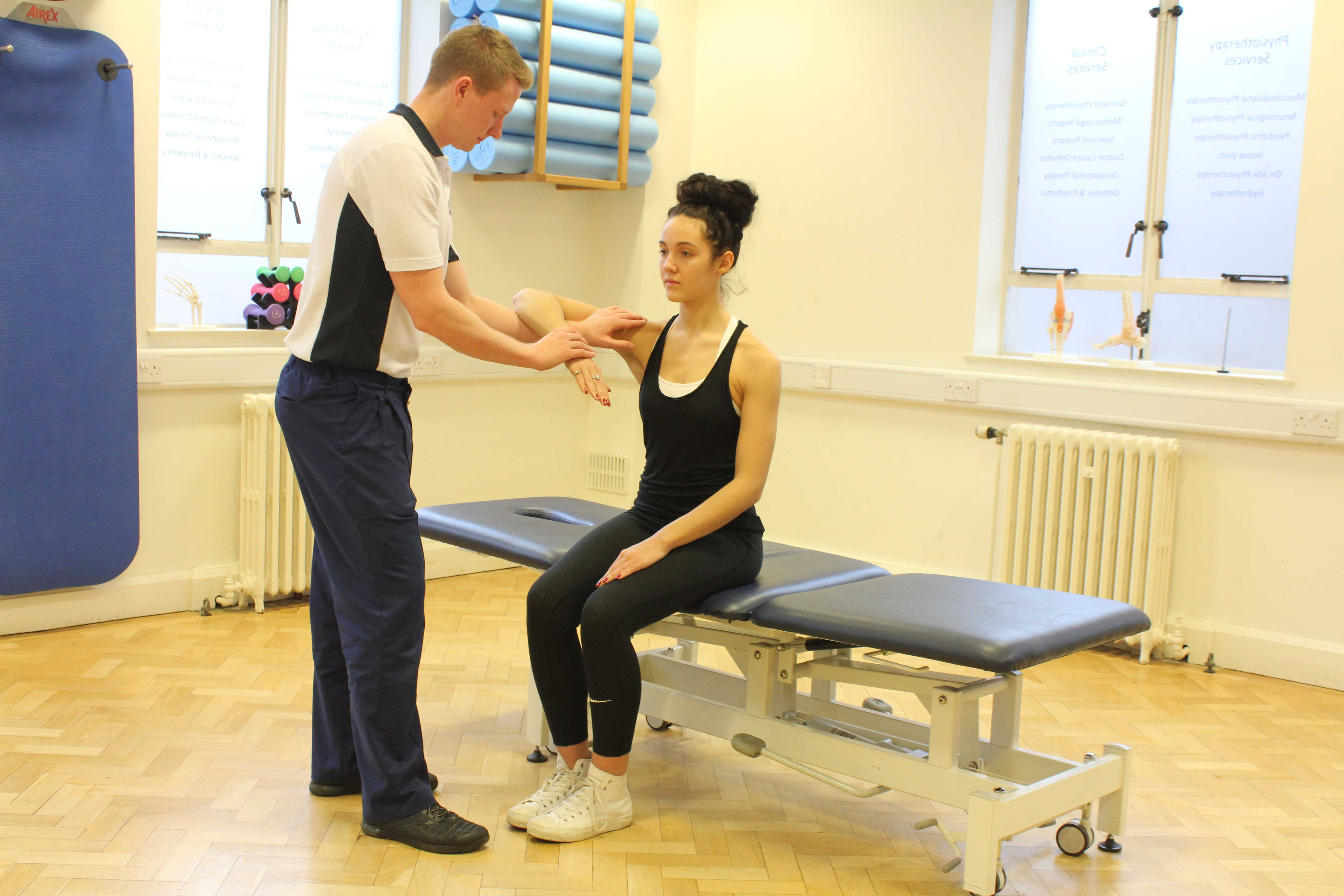 Specilaist musculoskeletal physiotherapst assessing a shoulder injury
