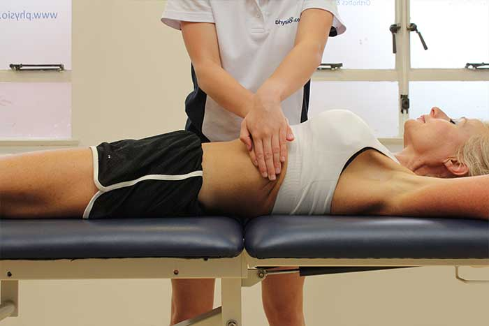 Customer reciving abdominal massage while in relaxed position in Manchester Physio Clinic