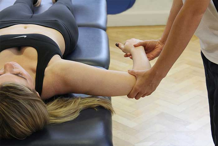 Customer reciving an upper arm massage while in a relaxed position in Manchester Physio Clinic
