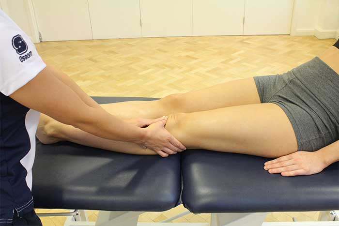 Customer reciving calf massage while in relaxed position in Manchester Physio Clinic