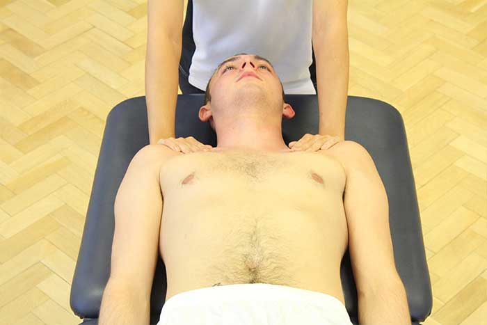 Customer reciving chest massage while in relaxed position in Manchester Physio Clinic