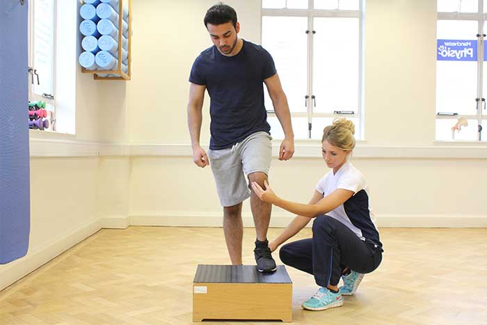 Customer doing leg muscle stretches while using a standing block in Manchester Physio Clinic