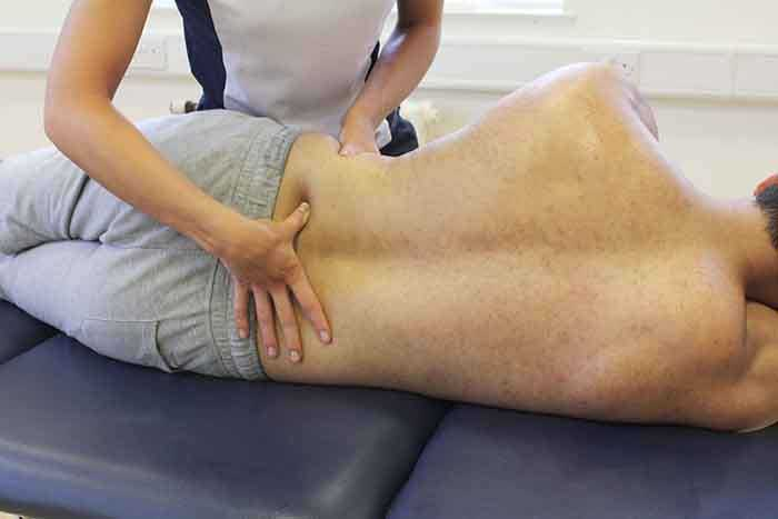 Customer receiving lower back massage while in a relaxed position in Manchester Physio Clinic